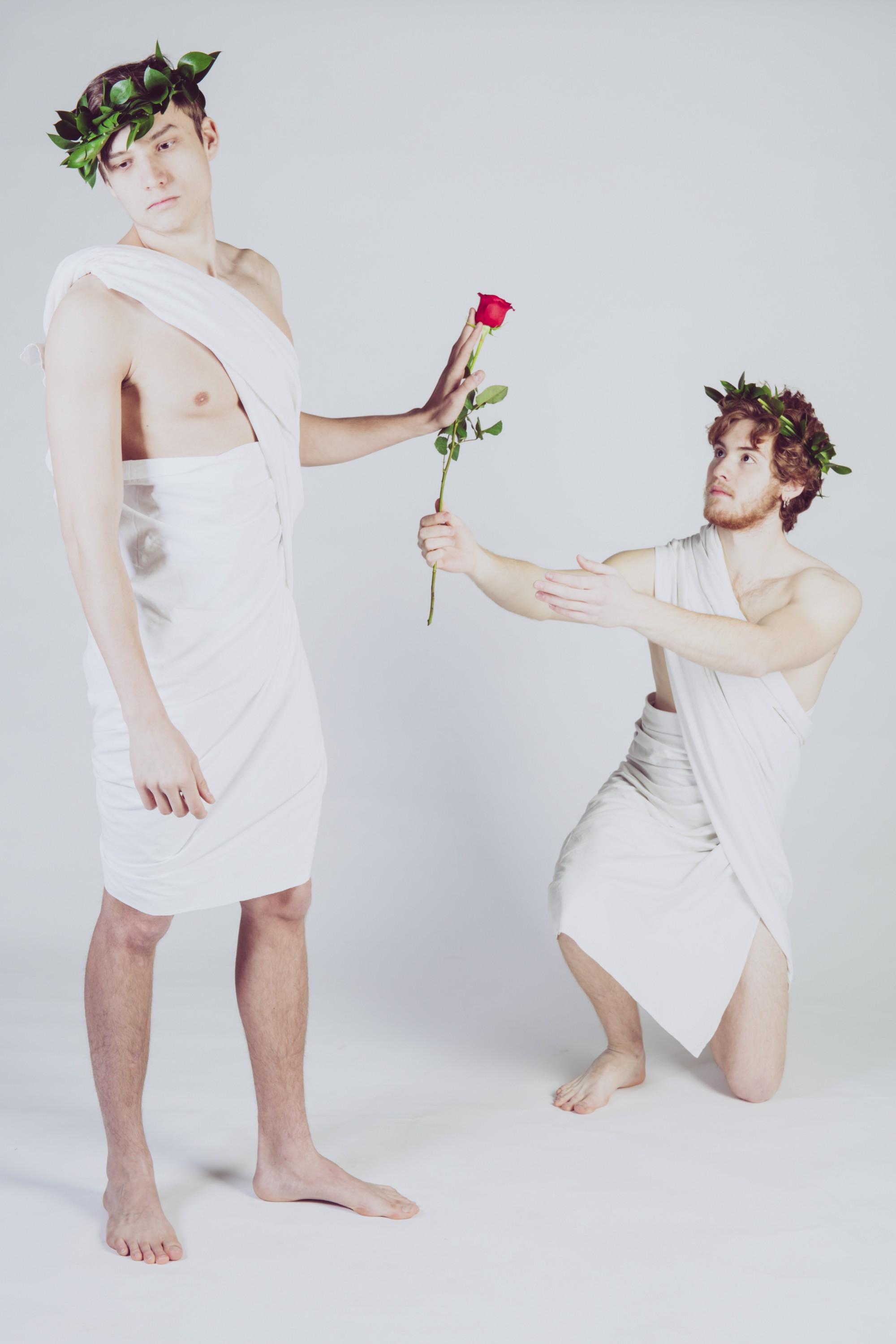 One person is kneeling and attempting to give a rose to a person standing looking disinterested and pushing the flower away.