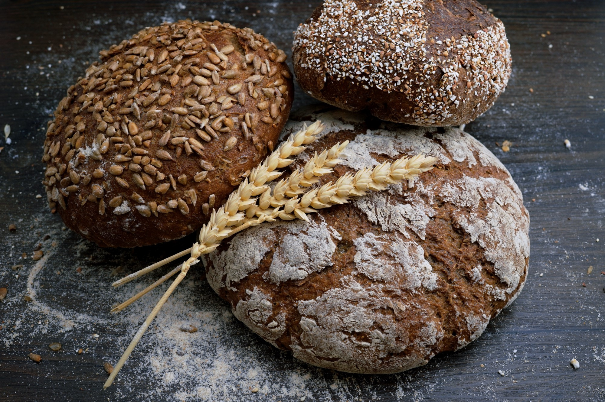 Three different kinds of round artisan bread on a lightly floured  table with three tassels of wheat laid crisscrossed on top artistically.