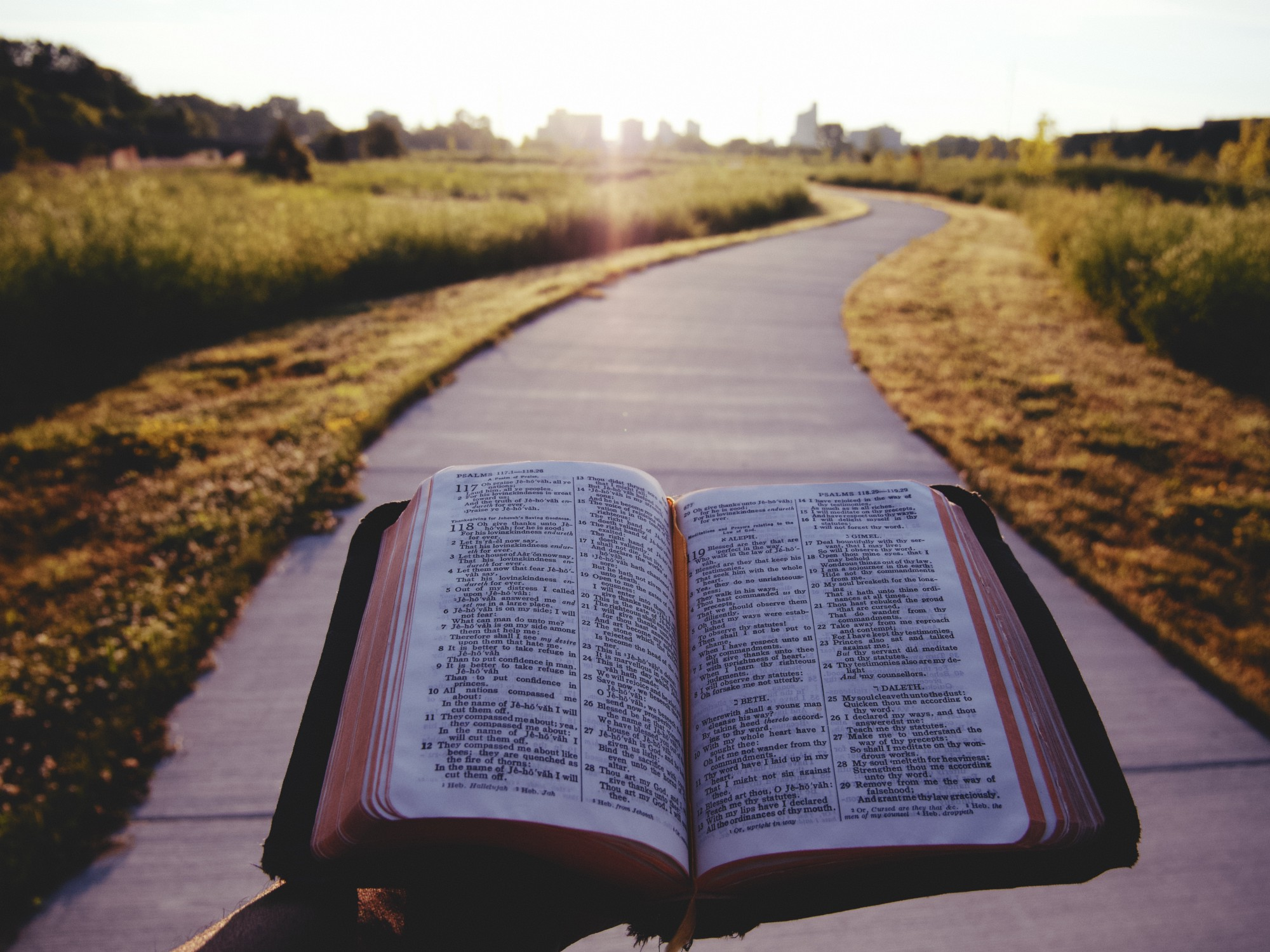 Man holding a Bible while standing still on a sidewalk