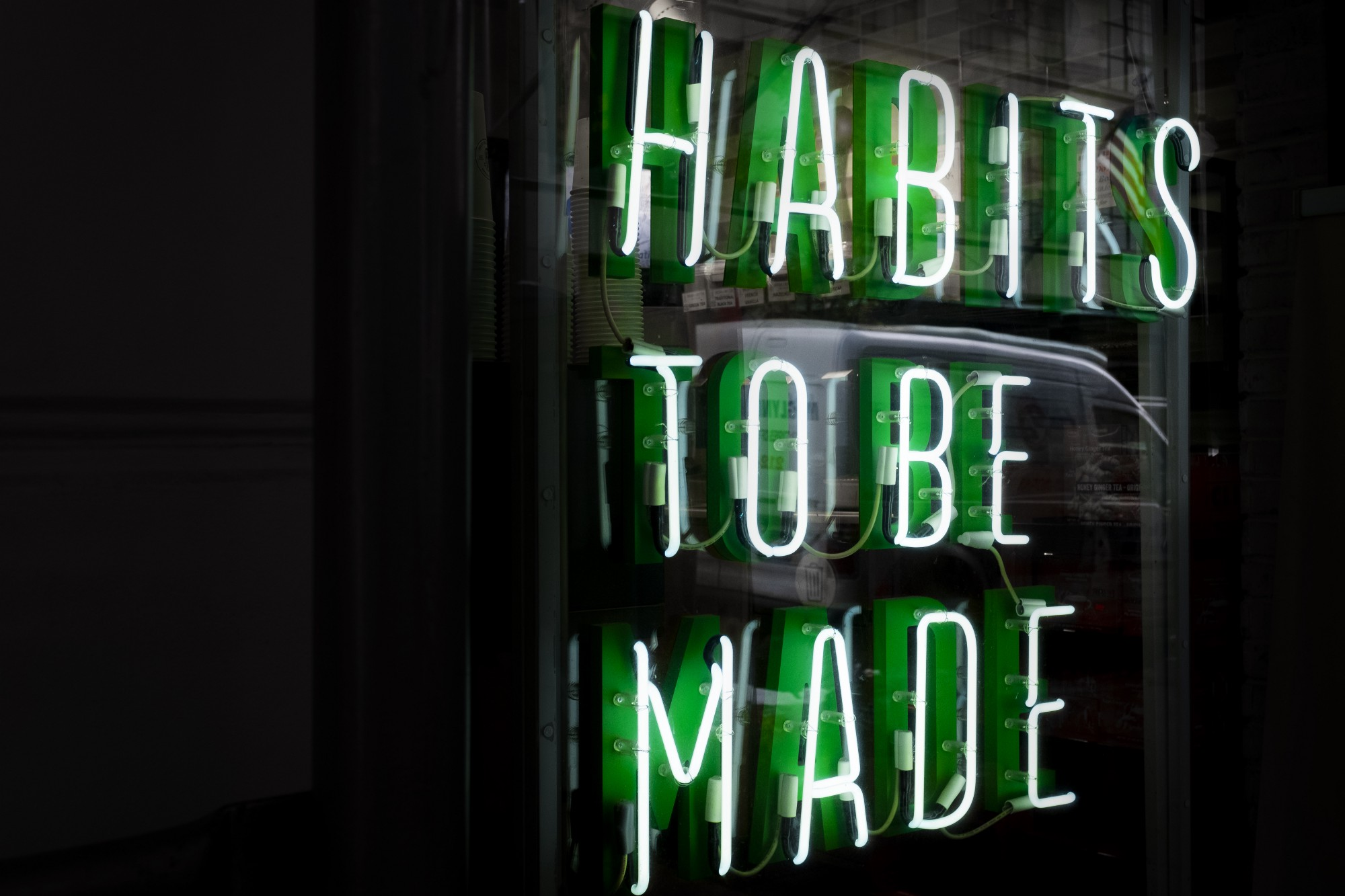 """The words """"Habits to be made"""" in neon light sign."""