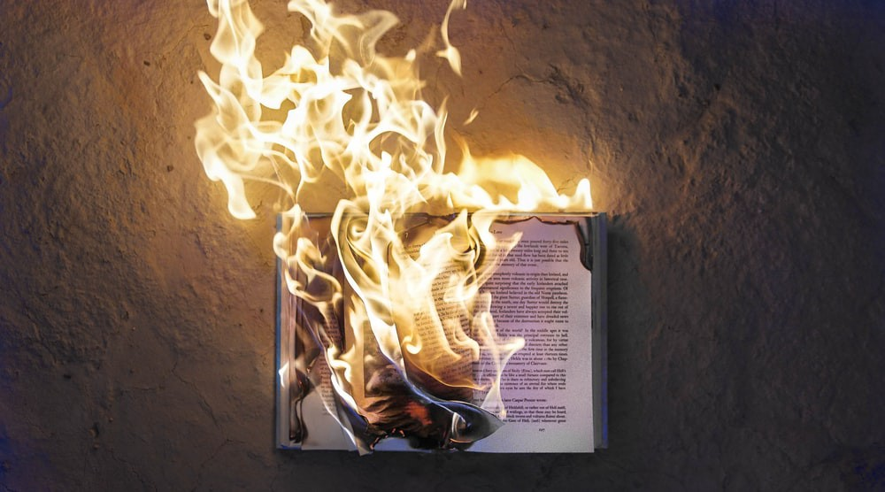 An open book engulfed in flames