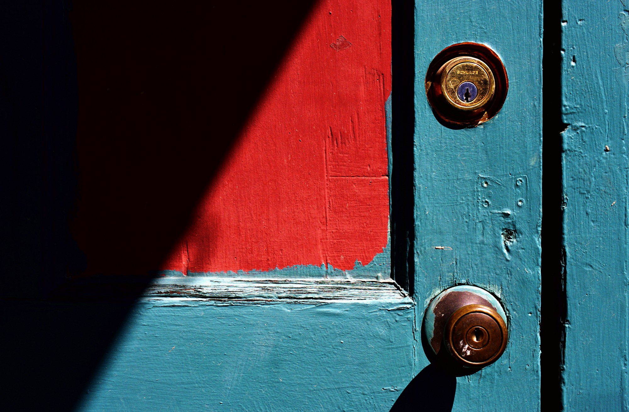 A battered door painted bright blue and red sports a brass doorknob and deadbolt.