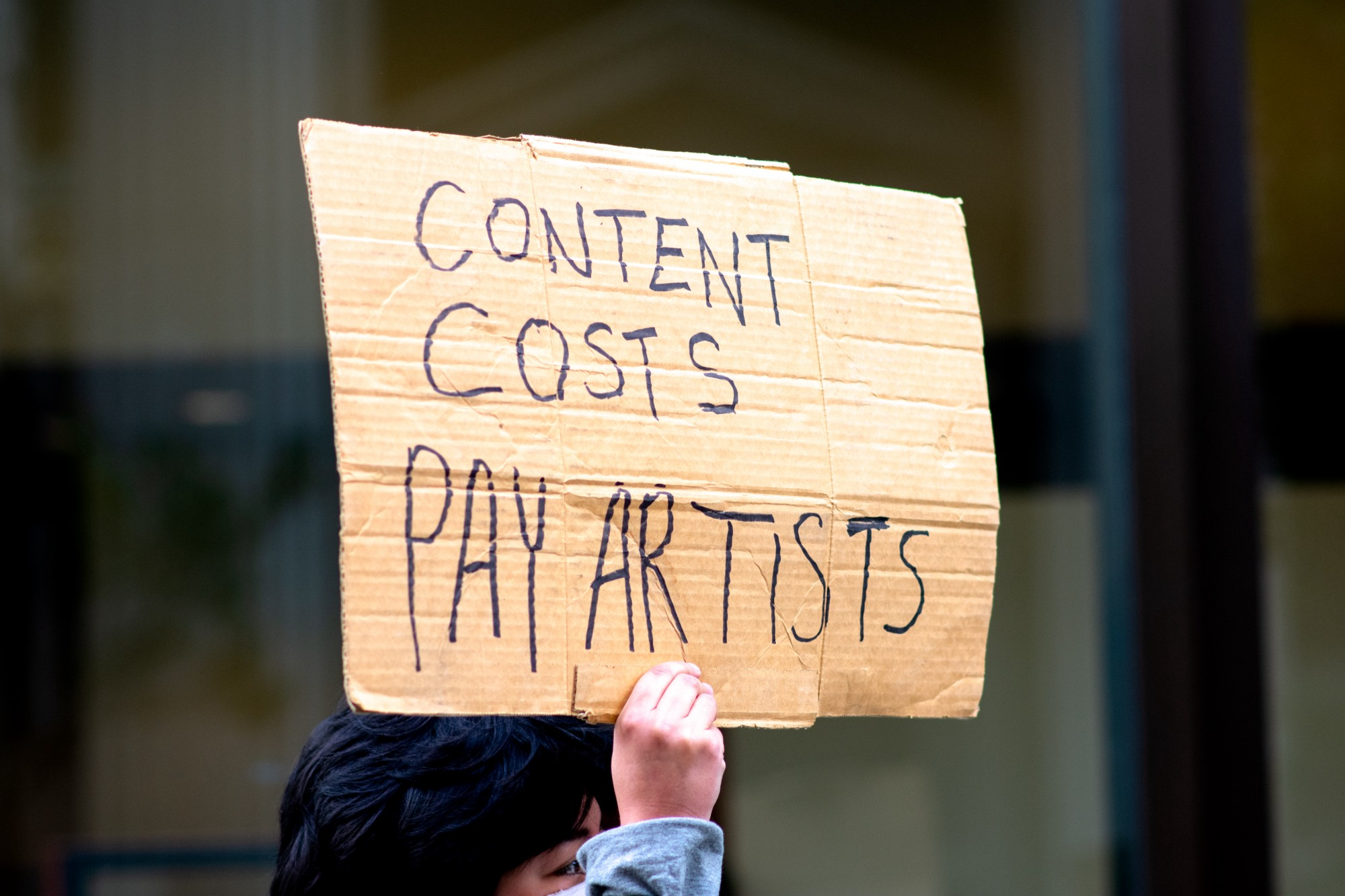 "Sign that says, ""Content Costs, Pay Artists"""