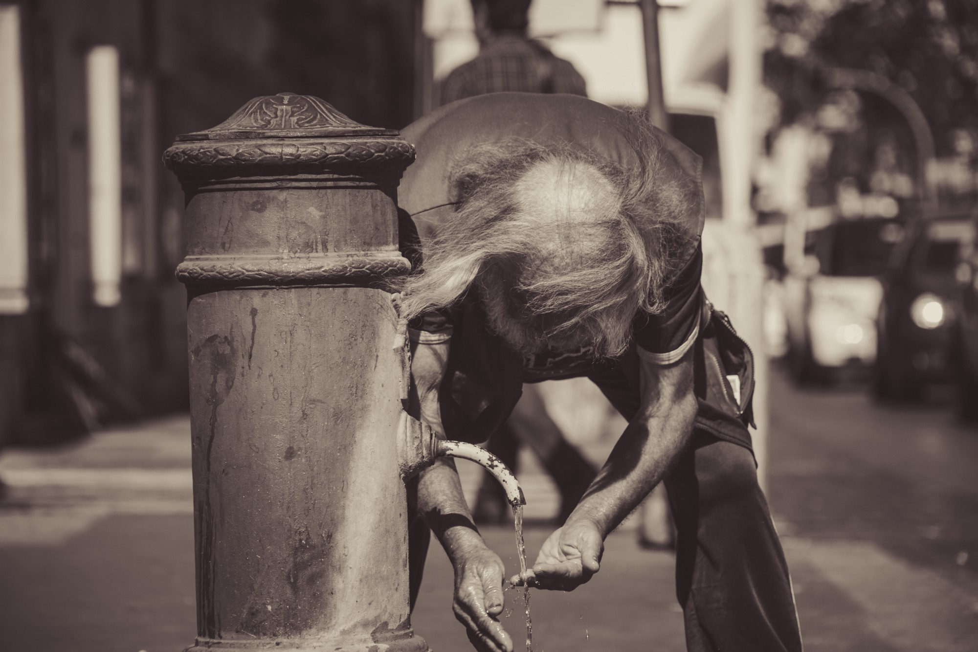 Elderly man with long hair but balding, washing his hands from a fire hydrant that is trickling a small stream of water.