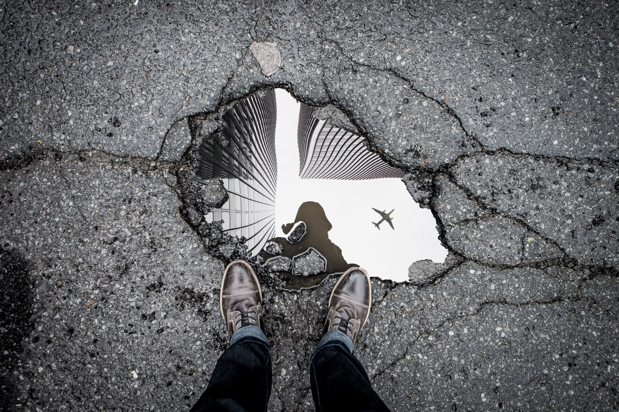 A person's feet near a glassy puddle of water in pavement. The person's reflection is visible in the puddle.