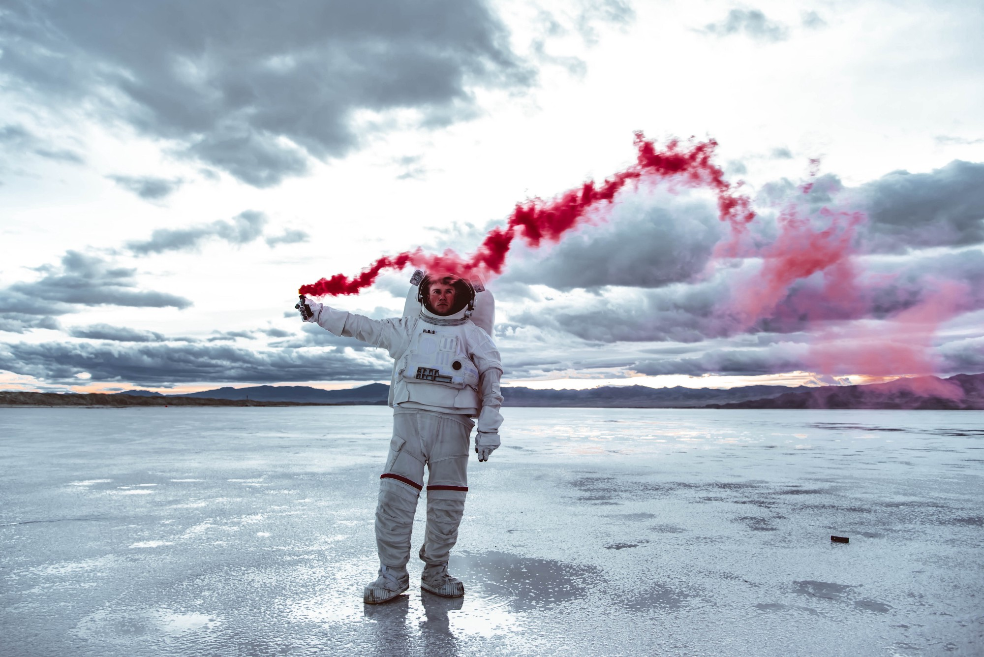 astronaut in a white spacesuit, holding a red flare