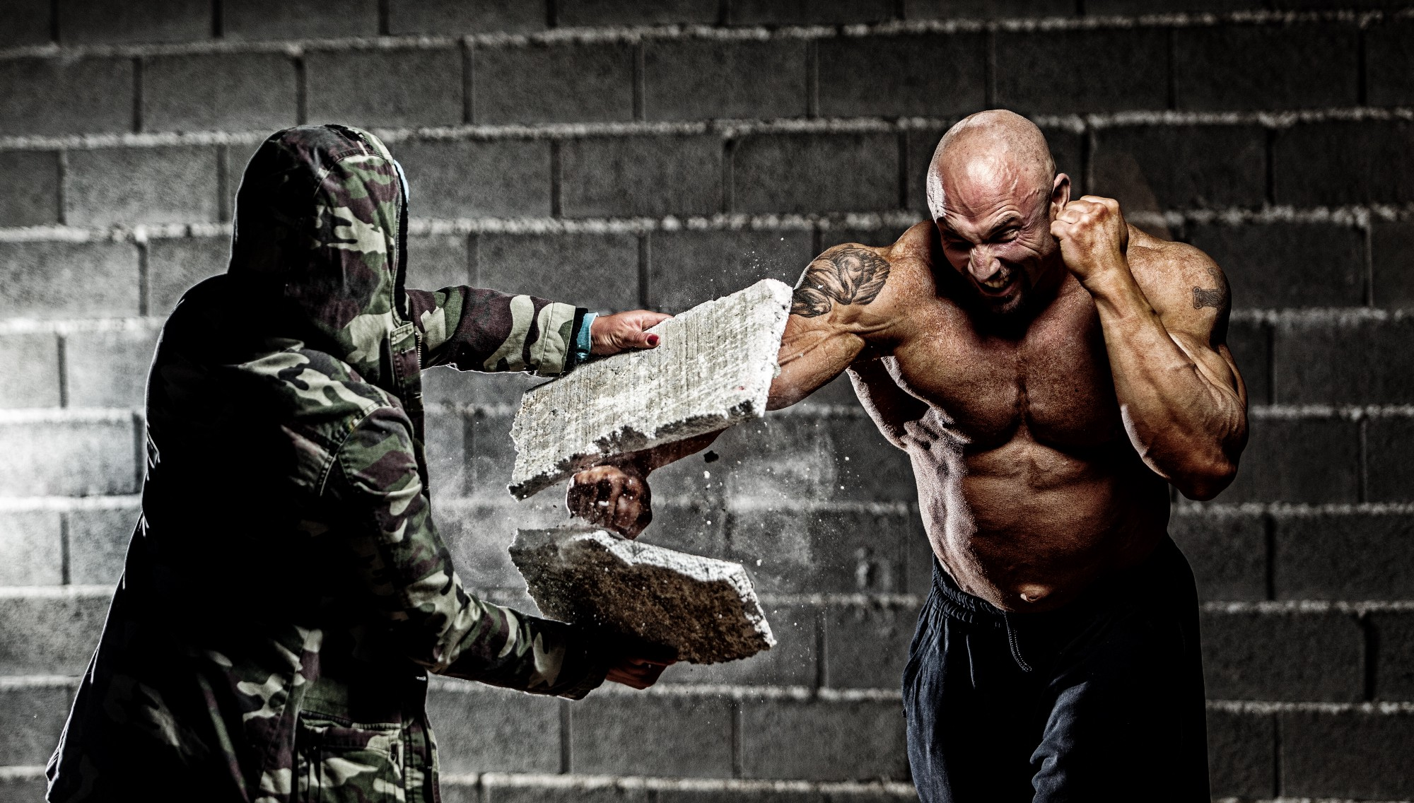 Hi there! BichoDoMato here. This picture displays a very muscular man (no shirt!—he looks like a fighter) breaking a long white brick in two, with fists! Another person is holting the brick being broken. That person is wearing a military suit.