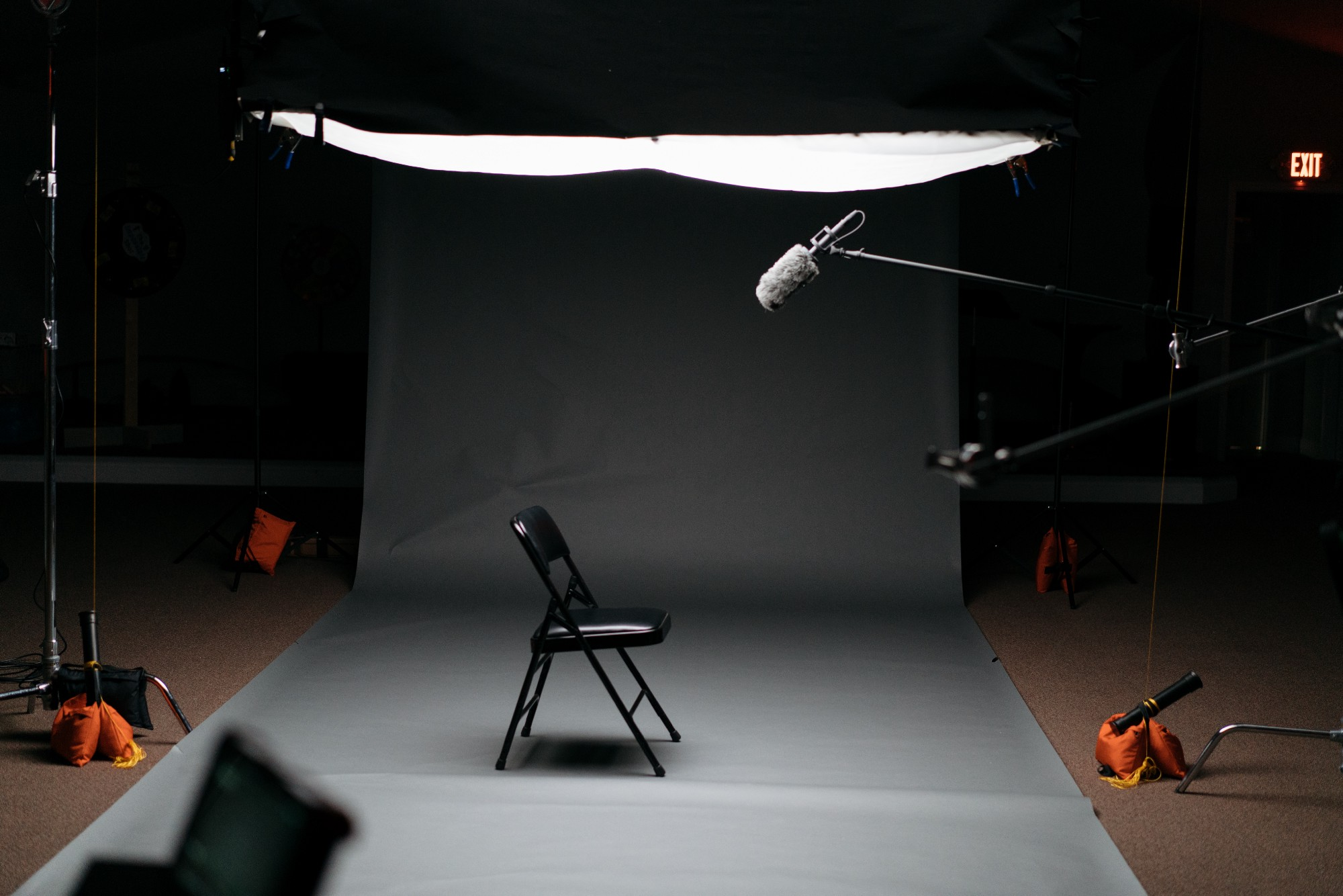 An empty set with a chair, a mic, and soft lighting waiting for someone to sit down.