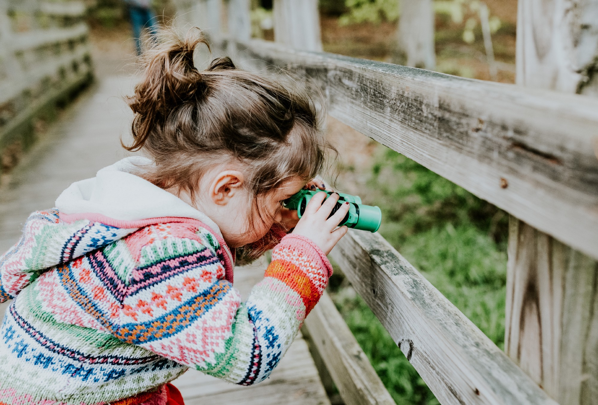 a little girl toddler standing on a bridge in her colorful winter sweater looking through her green binoculars curiously.
