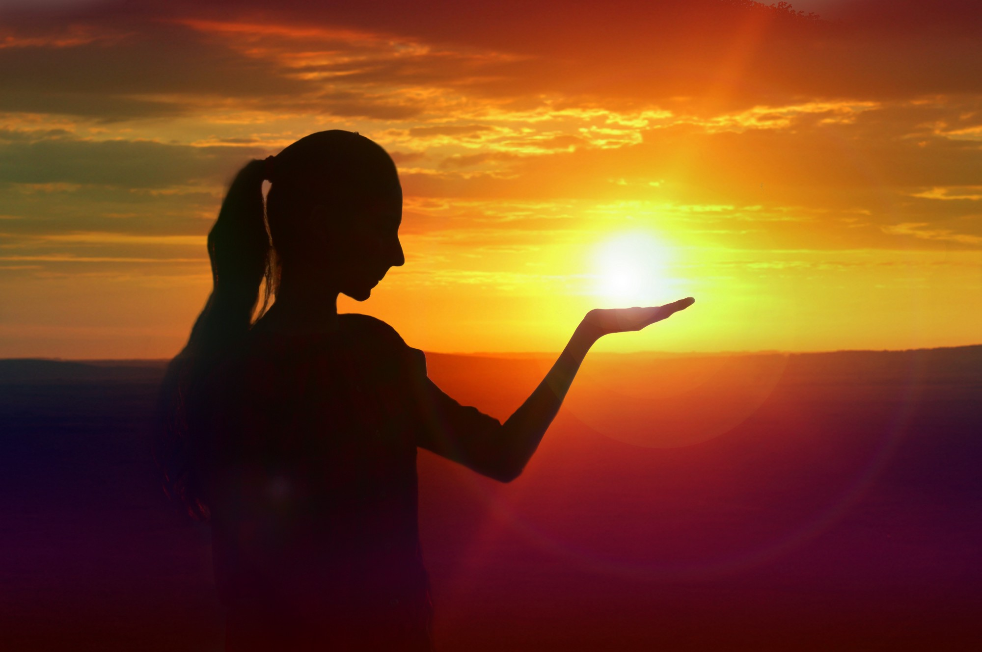 Silhouetted woman that appears to be holding the sun in her hand.