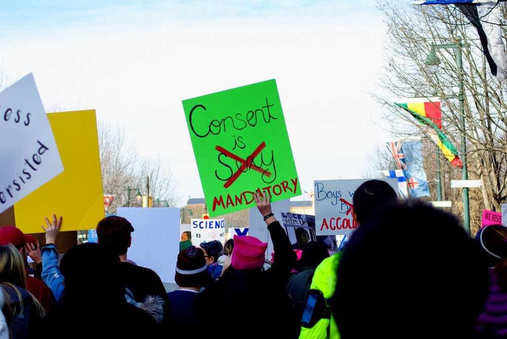 """Royalty-free stock photo ID: 1780159370  Philadelphia, PA / USA - 1/20/2018: Women's March demonstrators on the Benjamin Franklin Parkway. Woman holds a bright green sign that reads: """"Consent is sexy (crossed out) mandatory"""""""