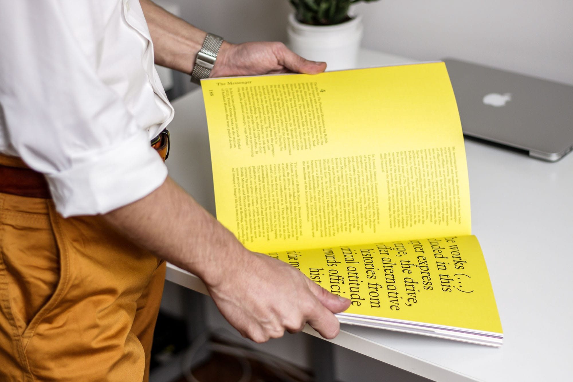 A person opening a book with pages in yellow showing beautiful typography