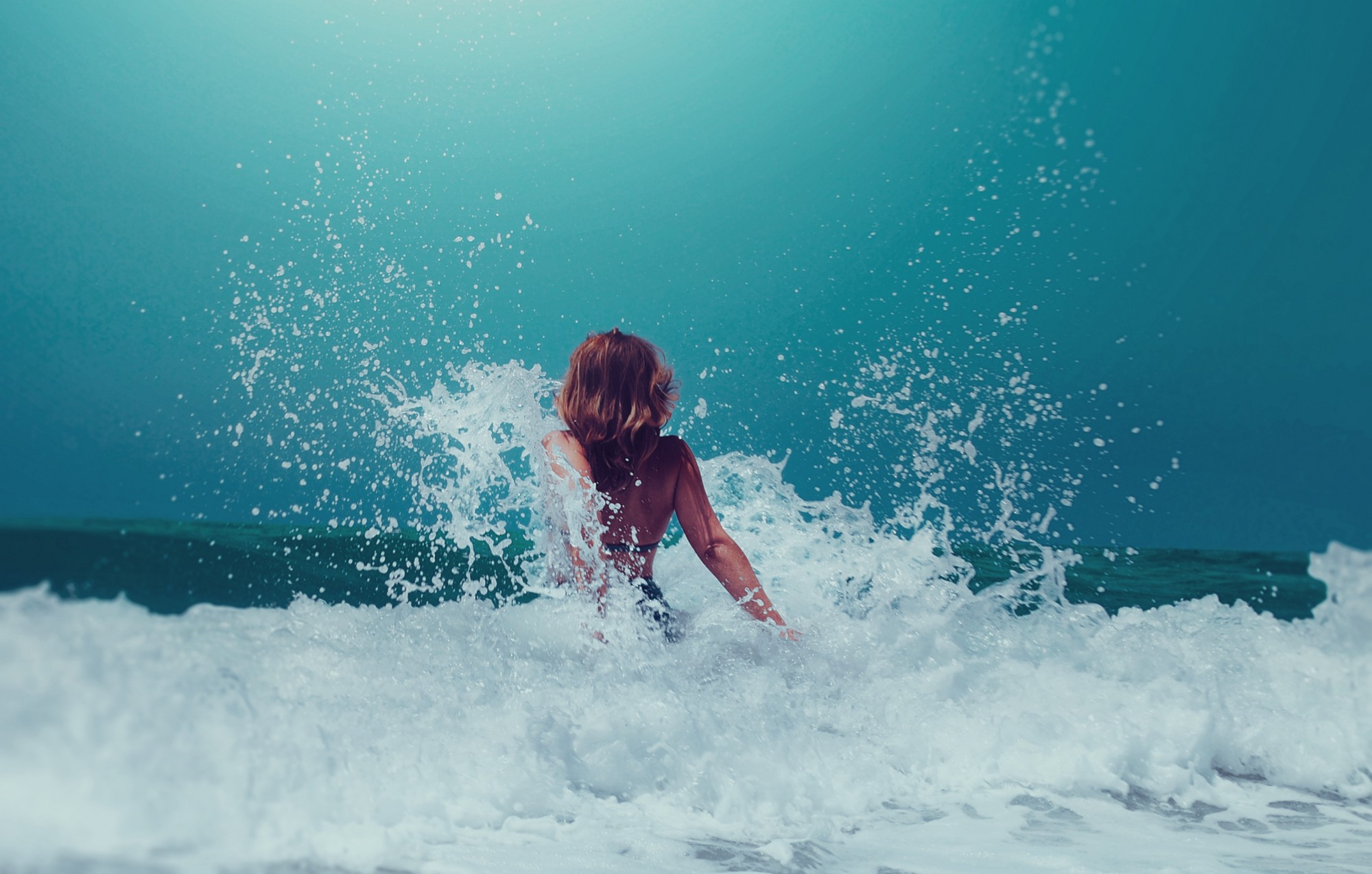 a young woman rushes forwards into a crashing wave
