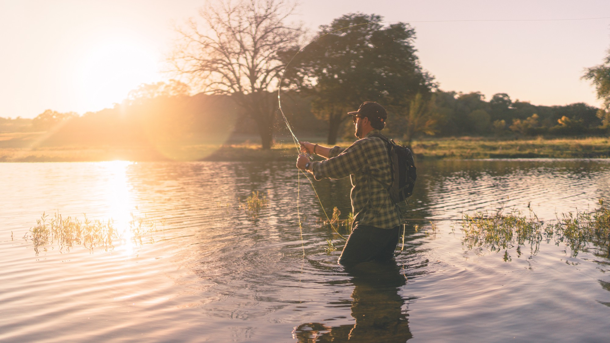 A man fishing while the sun is rising
