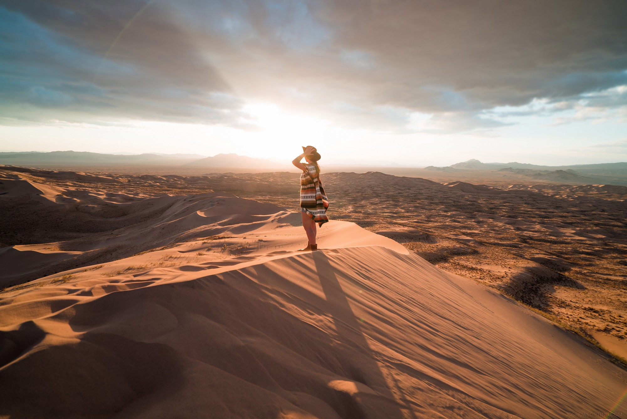 An inspiring writer on Medium looking over sand dunes at the setting sun in a desert.