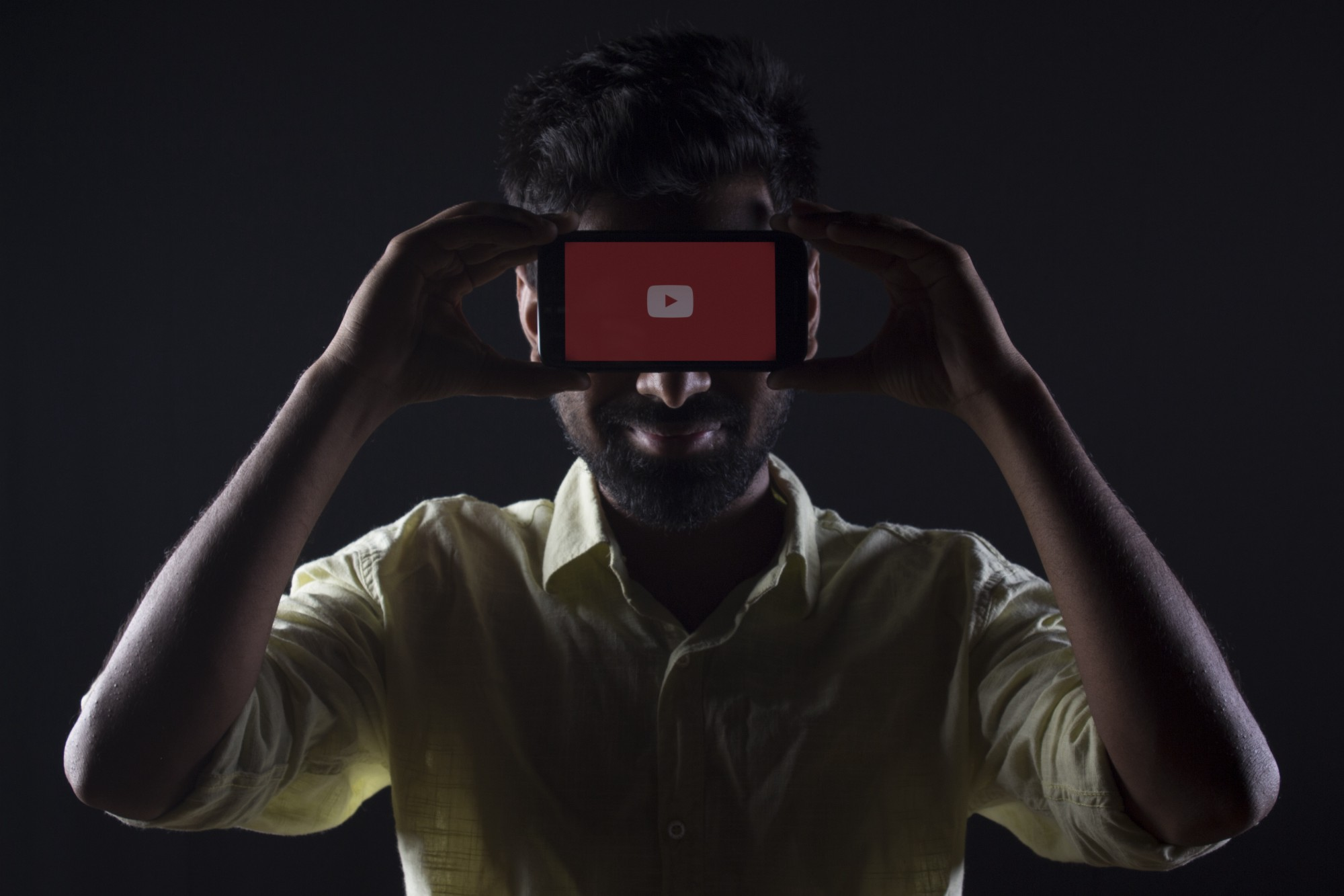 A man, dressed in a yellow button-down shirt, is holding up a phone to his forehead that has the YouTube logo on the screen.