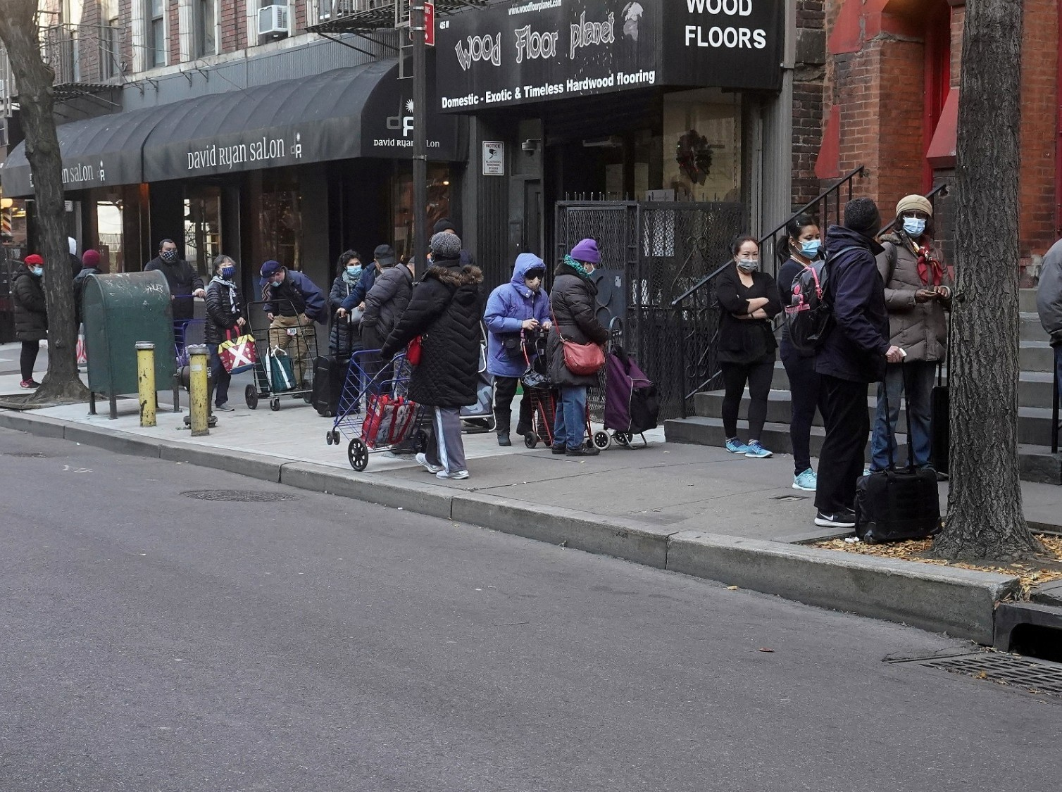 People wait in line at the St. Clements Food Pantry in New York City, December 11, 2020. Photo by Carlo Allegri/Reuters