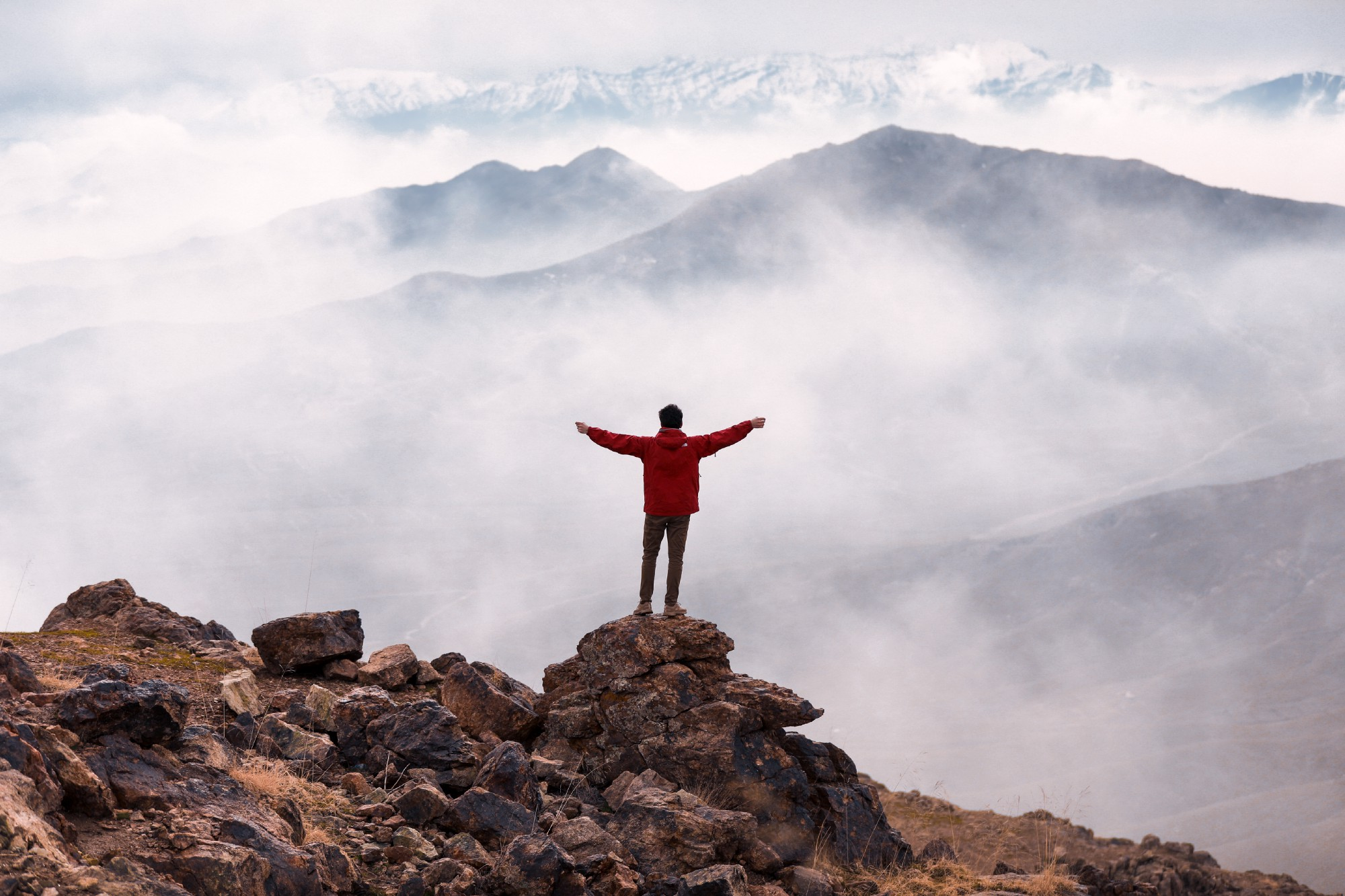 The back of a person wearing a read hiking jacket, standing arms outstretched, facing an ocean of mountains and clouds.