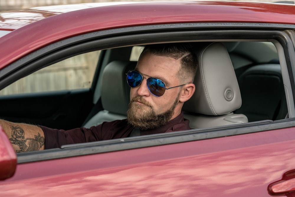 A man in obnoxious sunglasses stares with a gimlet eye from the window of a car.