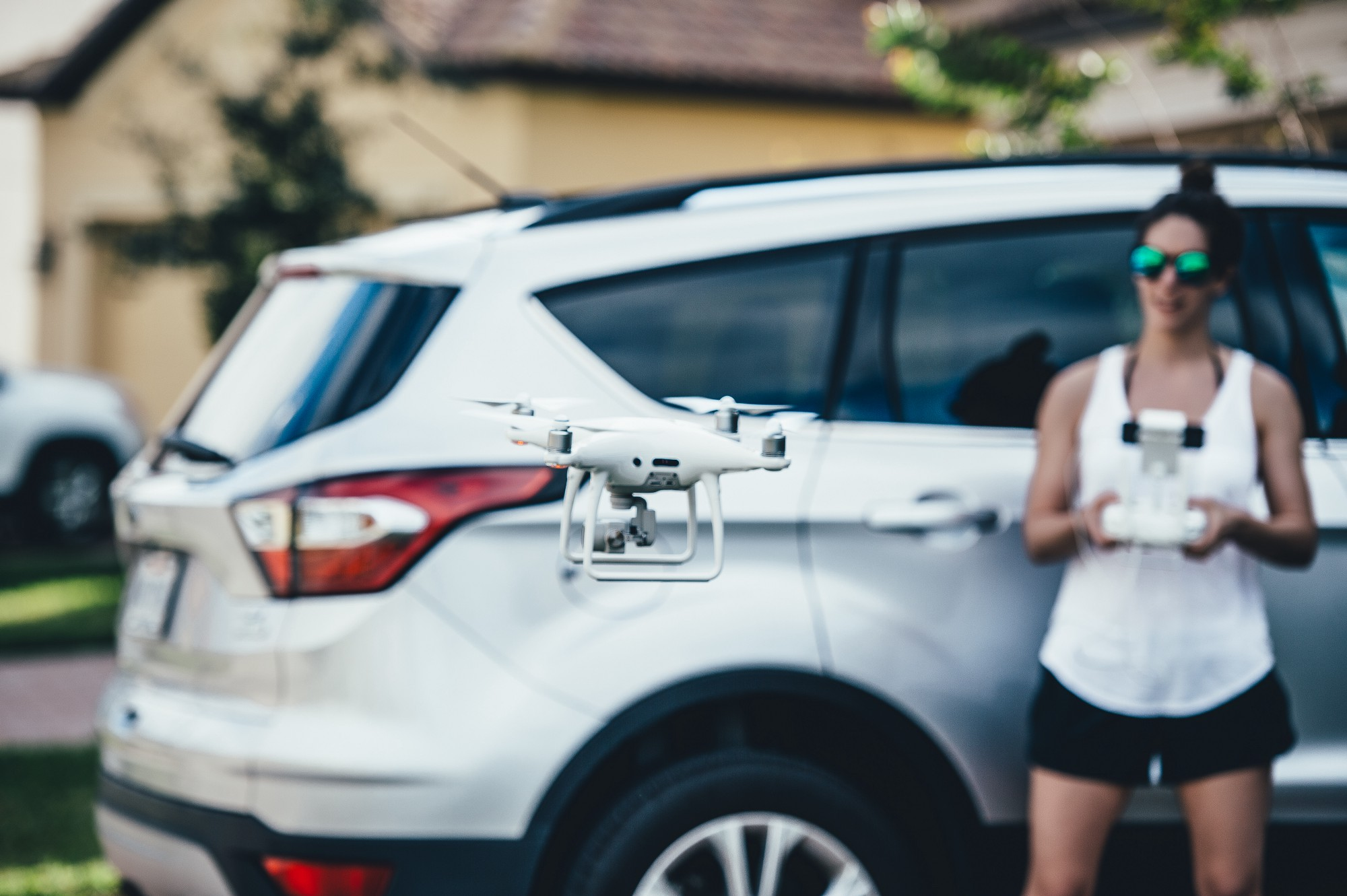 Woman standing in a driveway with her back to a light SUV while operating an aerial drone that hovers at shoulder height.