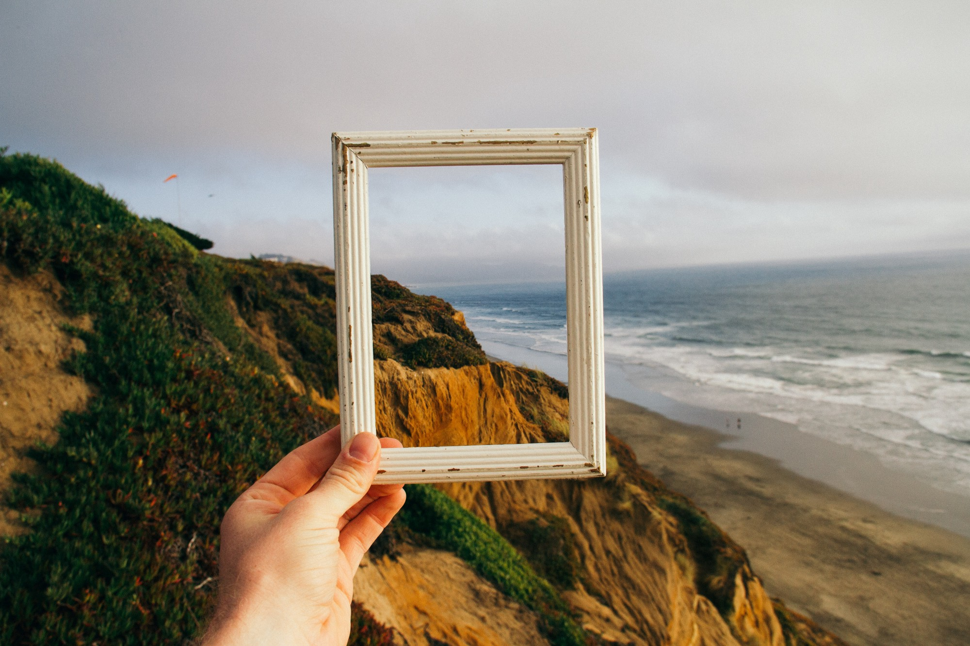 Person holding up empty frame to ocean view with cliff.