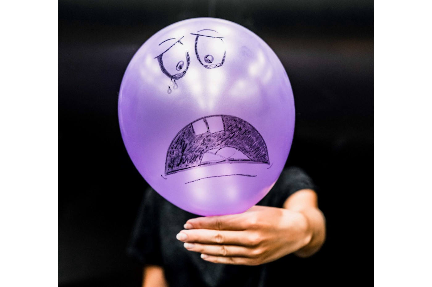 A man holds in front of himself a purple balloon with a crying face drawn on it.