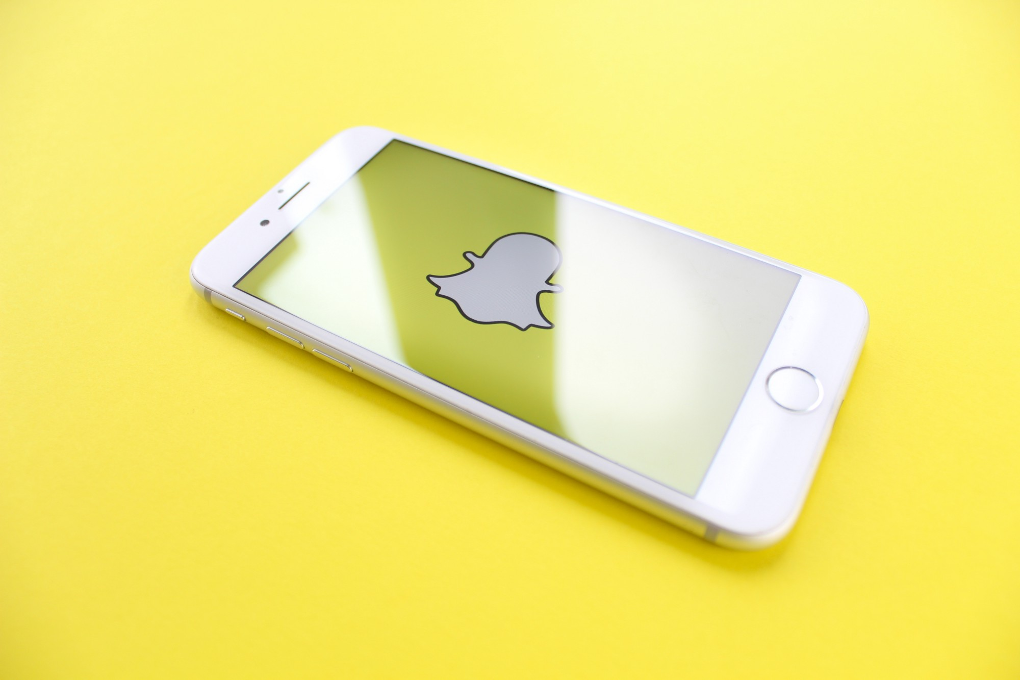 iPhone on yellow surface displaying Snapchat logo