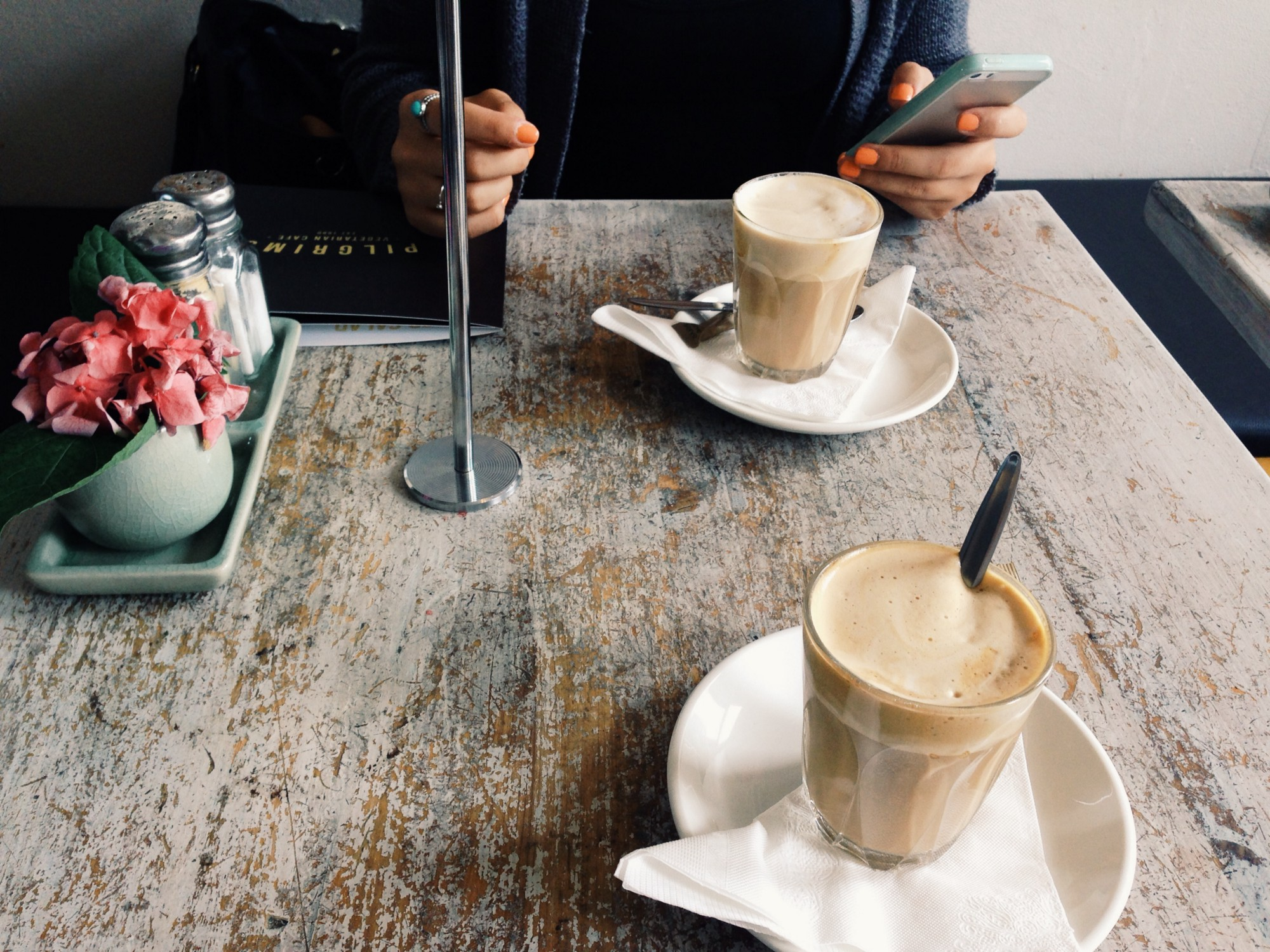 Image of a square, 2-top café table, with two cappuccino's and a person seated on one side holding a cell phone.