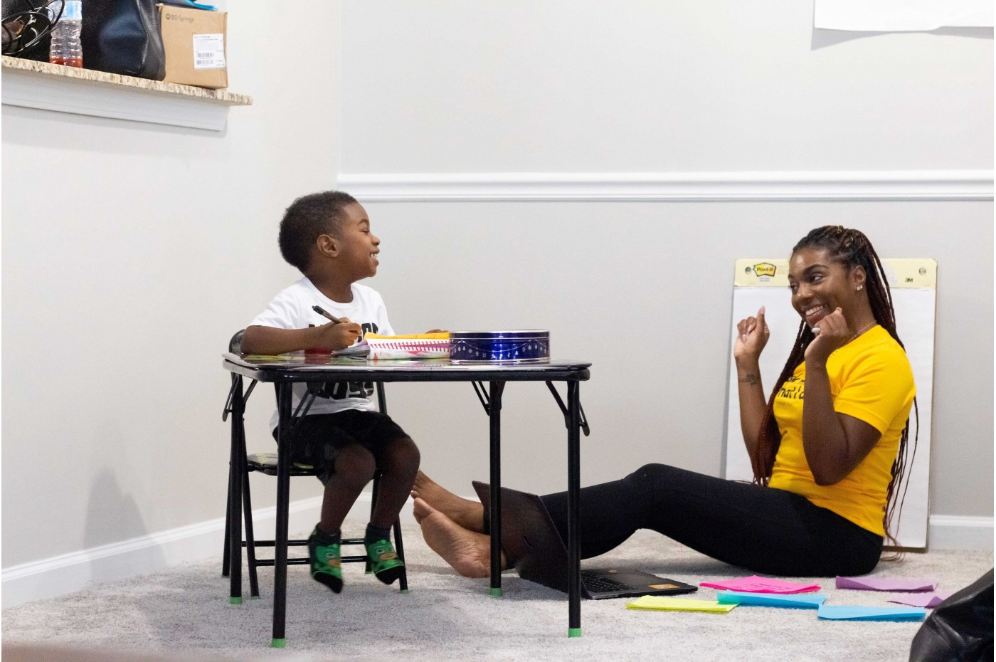 A woman sitting on the floor, encouraging a young child who sits at a desk near her.
