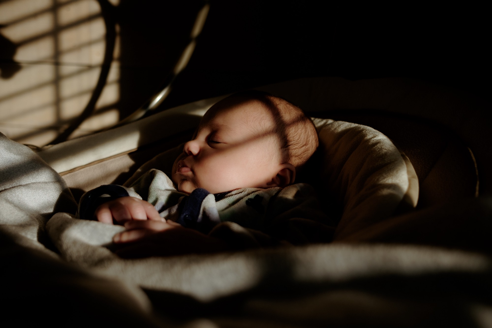 An infant sleeps in the shadows.