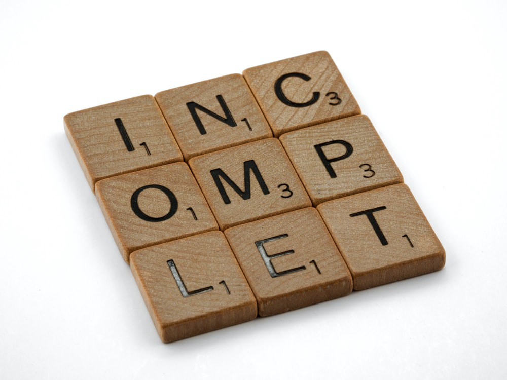 Scrabble tiles, jumbled, that spell the word Incomplet