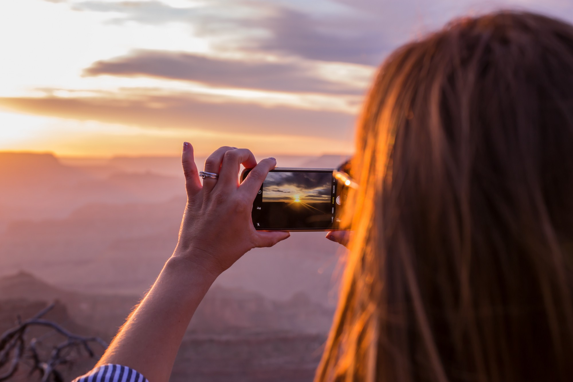Woman with camera taking picture of mountain sunset.