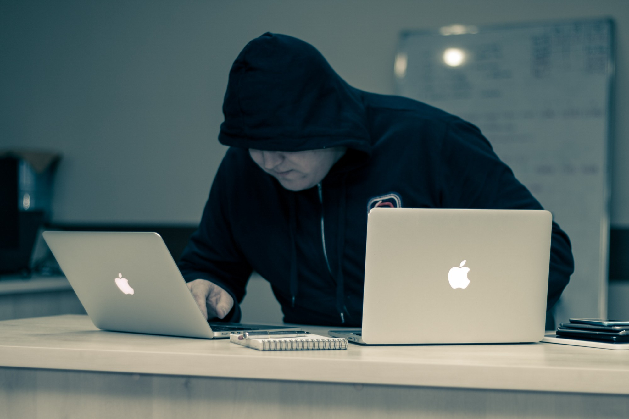 Hooded person uses two laptops, looking dodgy