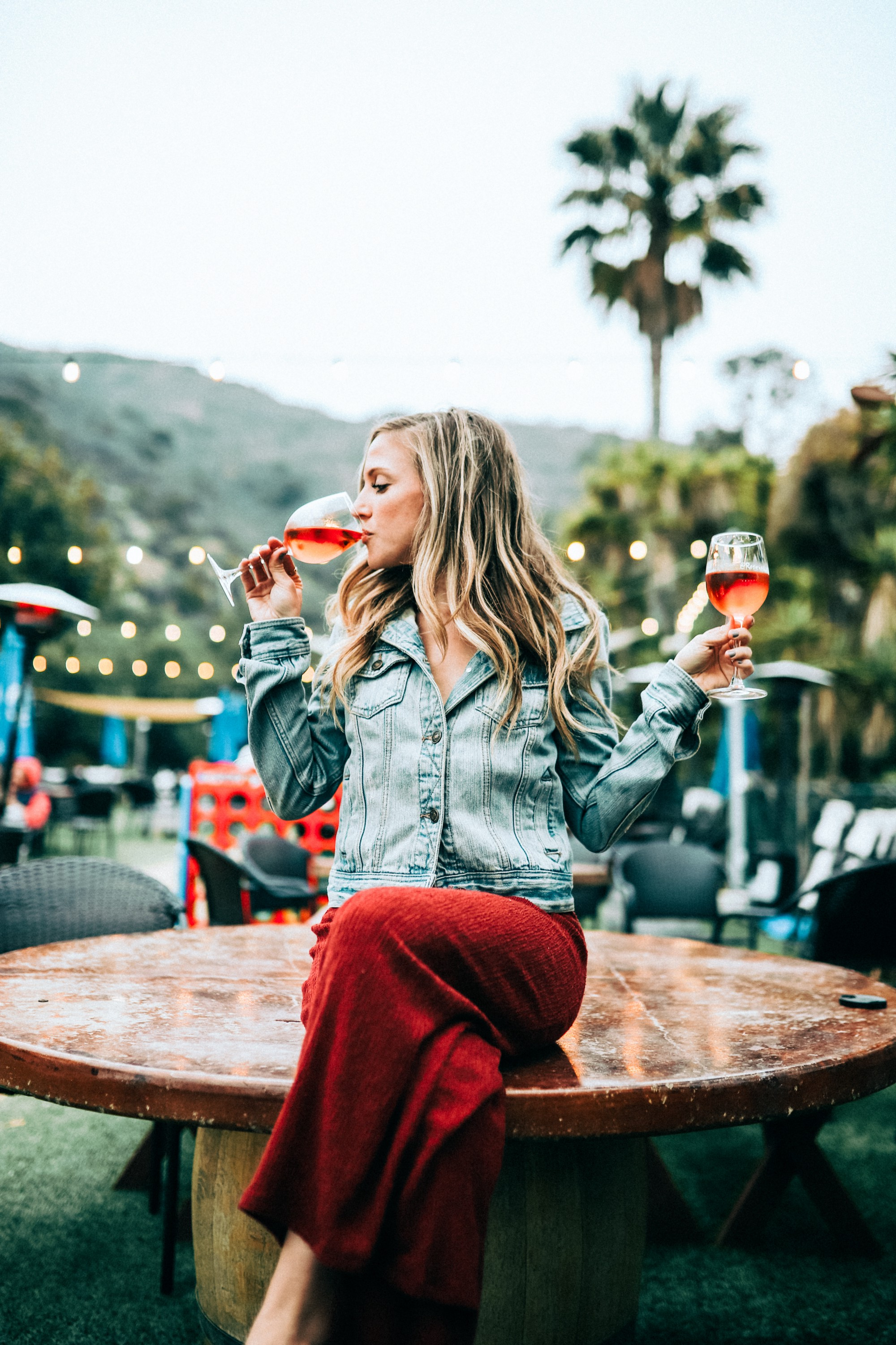 Woman holding a wine glass in each hand, while sipping from the one on the left.