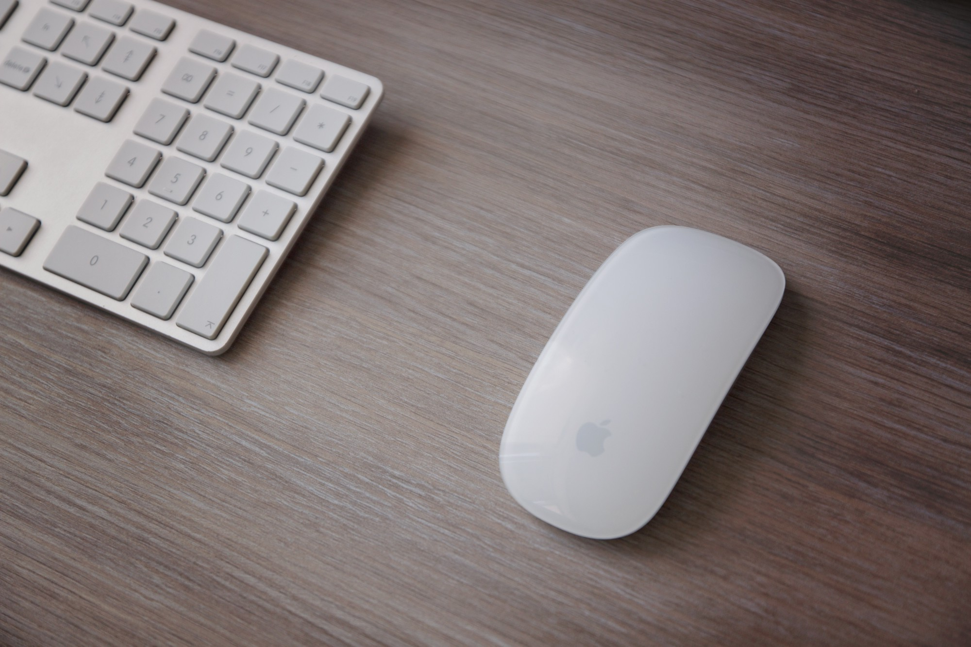 A mouse and keyboard on a wooden table