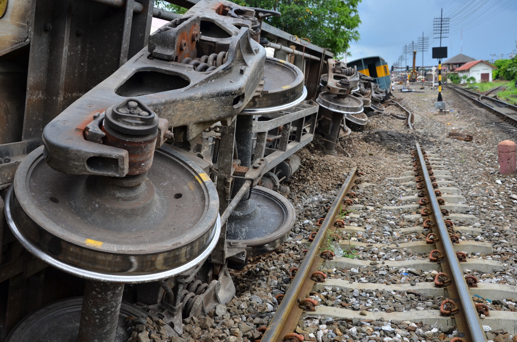 A major train derailment with freight cars lying on their sides beside the damaged railway track