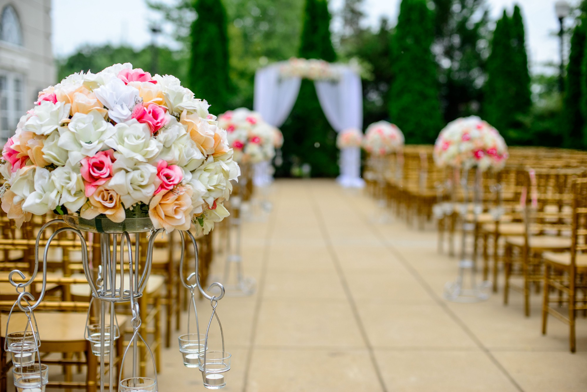 The setting for an outdoor wedding. Wooden seats have been lined up either side of the aisle. In the foreground is a large arrangement of pink, orange, and white flowers. At the fair end of the aisle stands an arch of white fabric. There are no people, as we are waiting for things to begin.