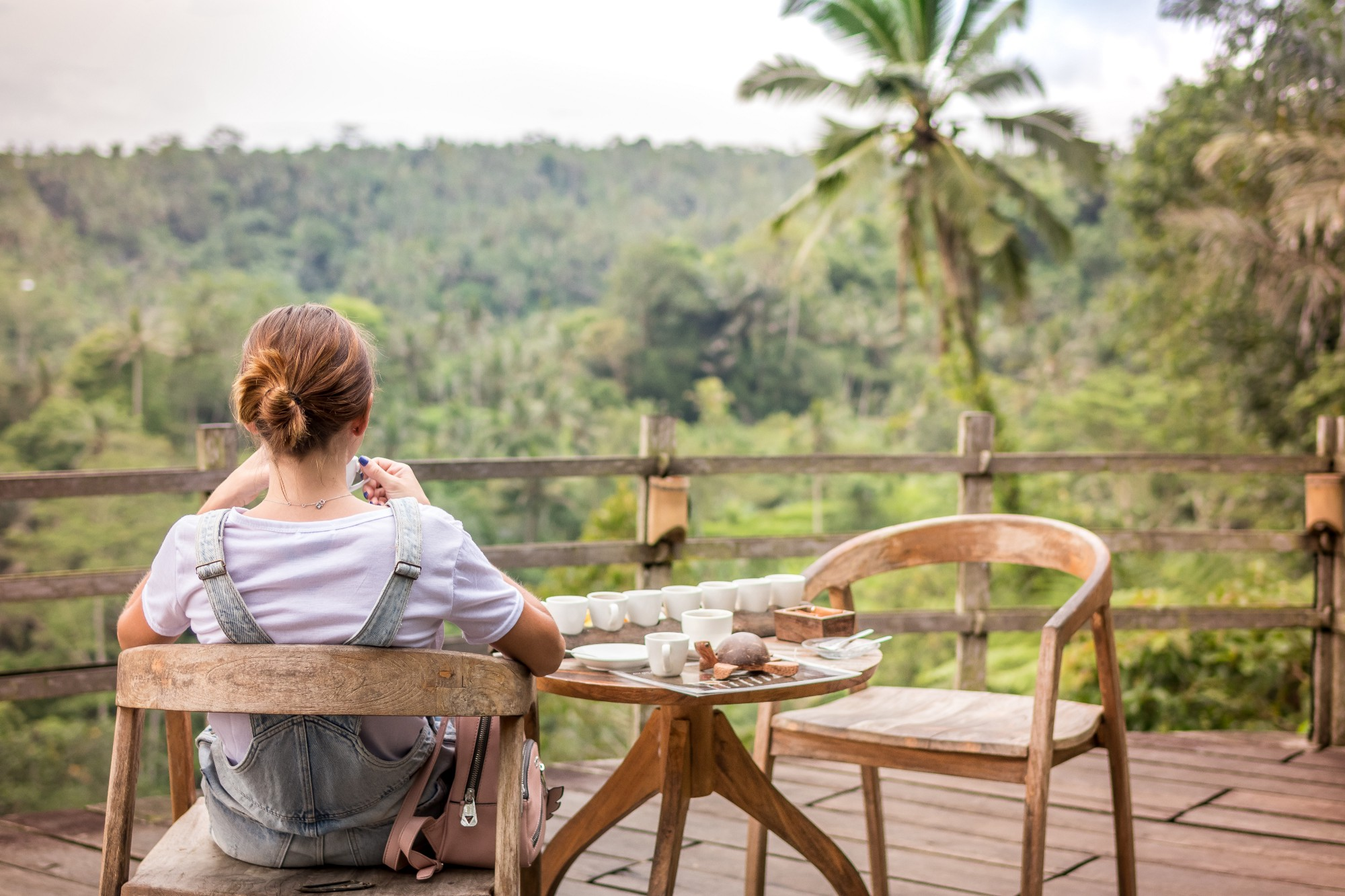 A woman sitting on a chair, next to a table of condiments, on a balcony, overlooking a jungle.