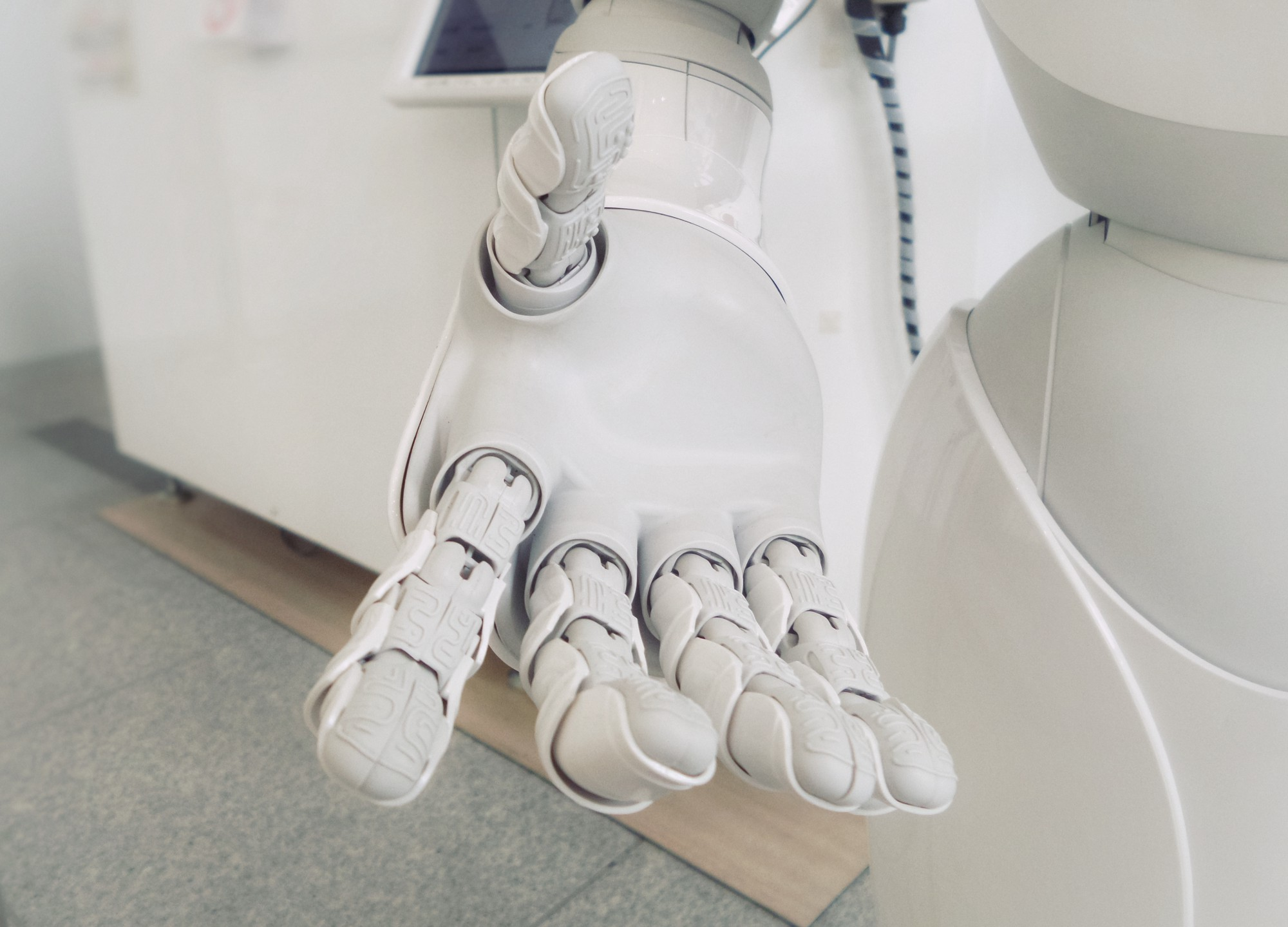 A robot hand reaching out as if to shake the user's hand.