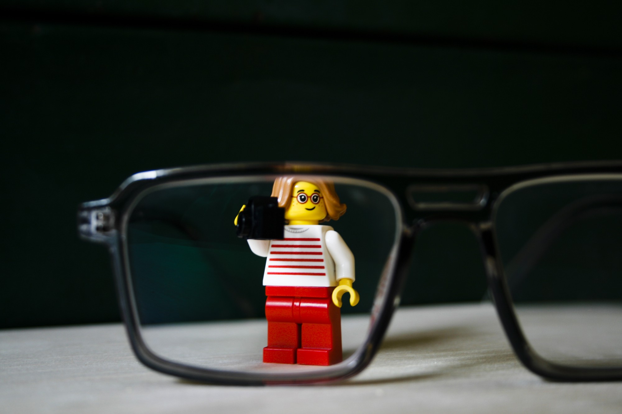 A lego woman wearing glasses peeks through a pair of glasses.