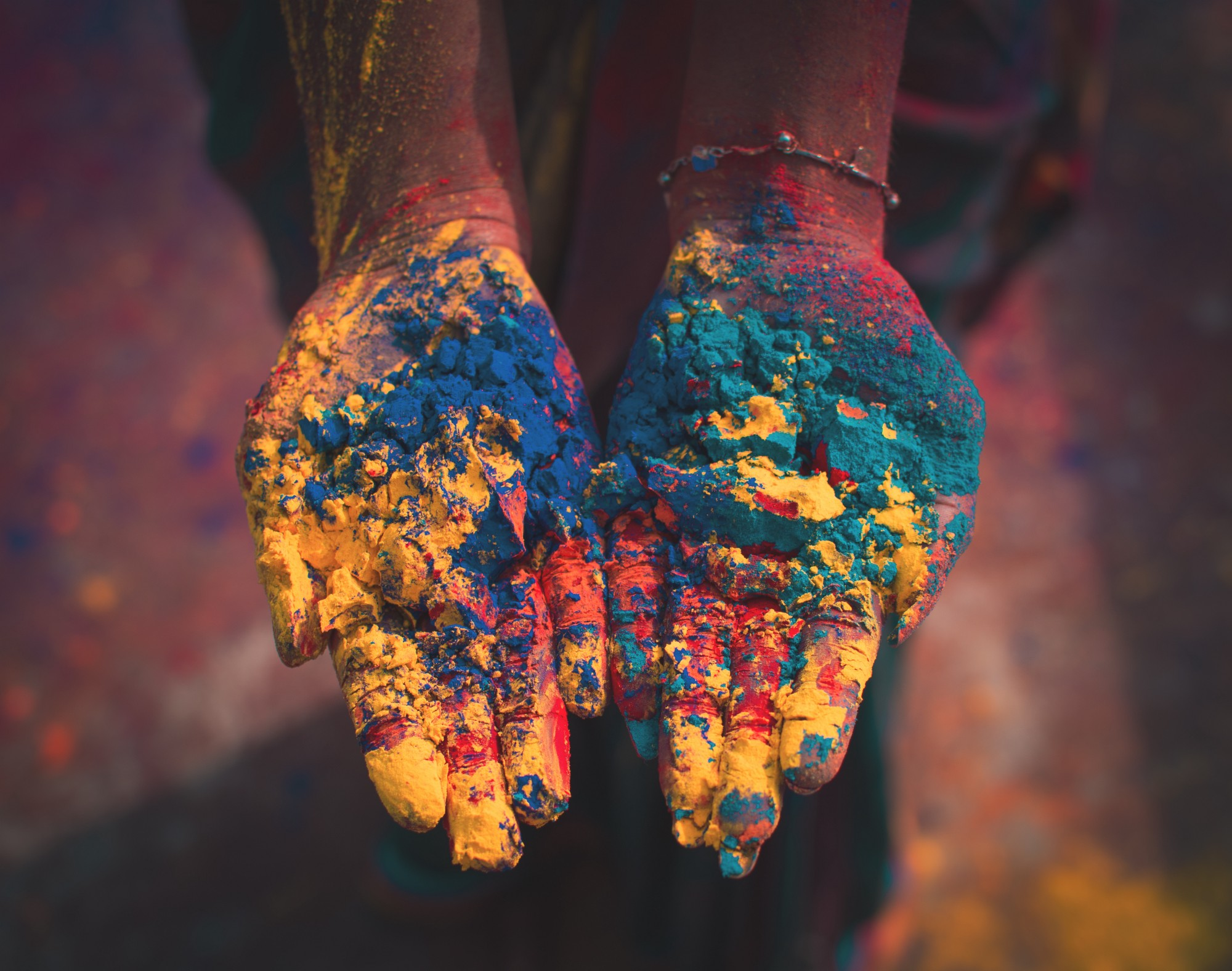 Colours of diverse citizens in a nation we weave in. Two hands coloured in Holi colours.