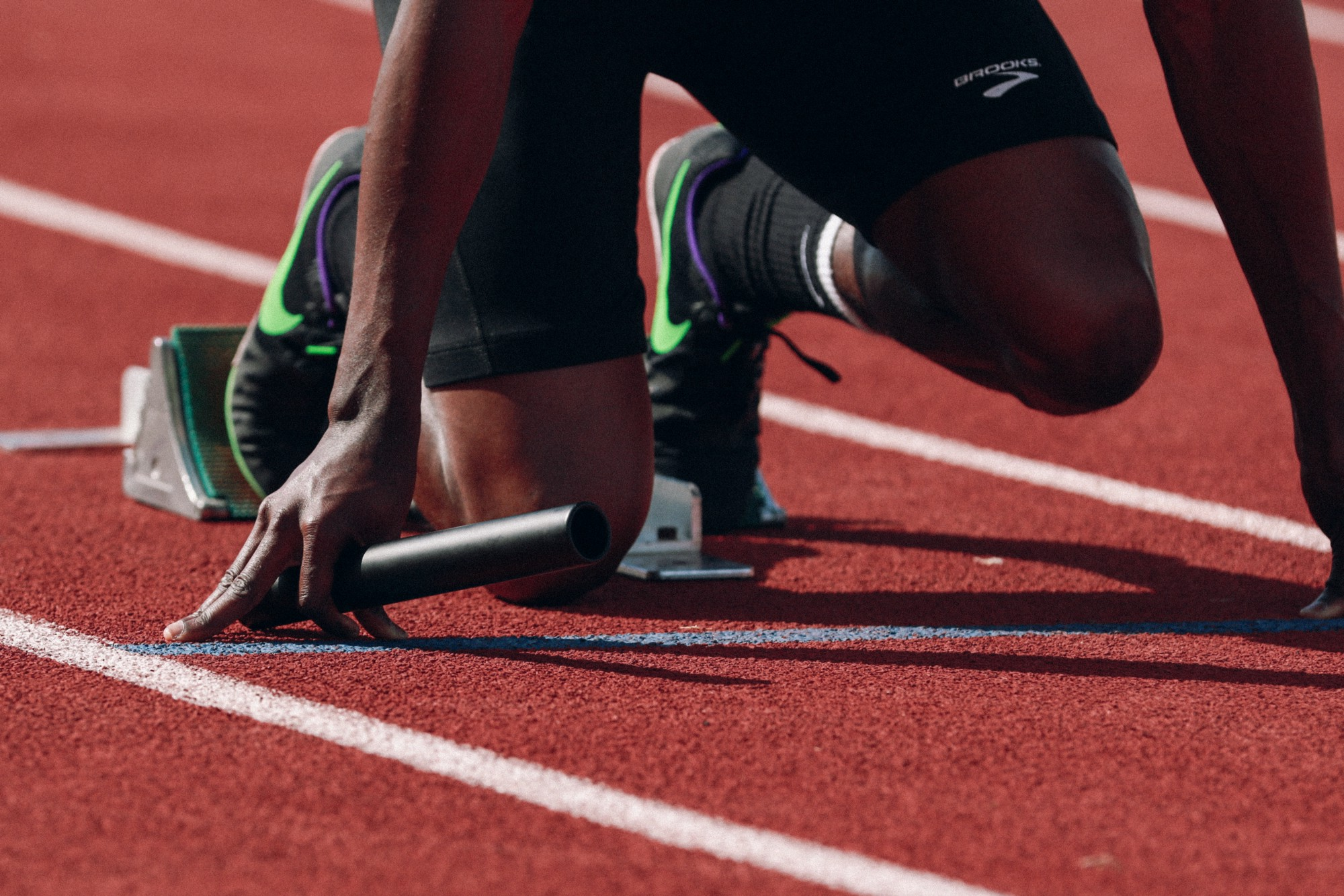 Legs and arms of a person in the set position on a running track. He's ready to run fast, but not age too fast.