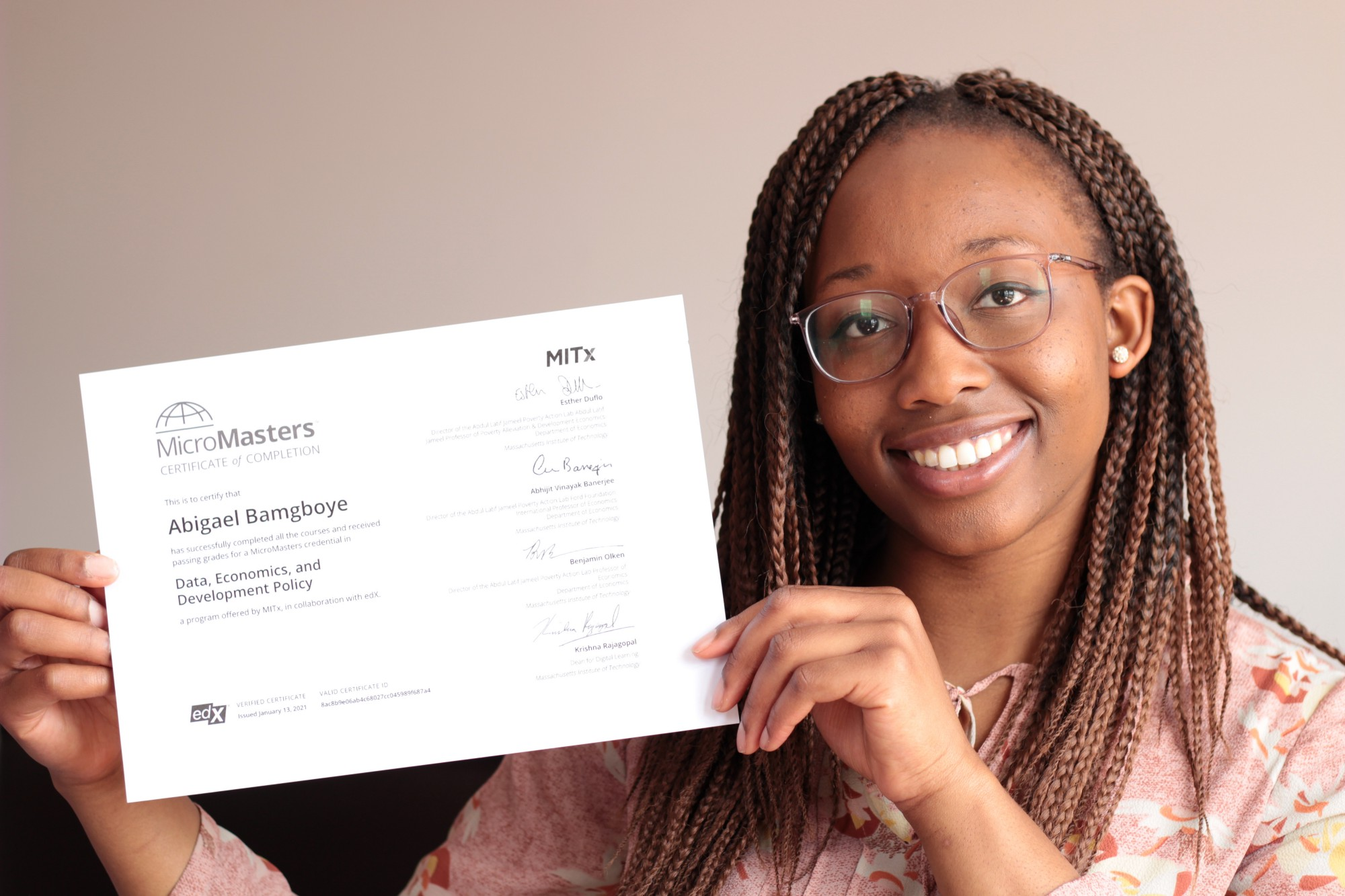 Young woman holds up an MITx MicroMasters program completion certificate.
