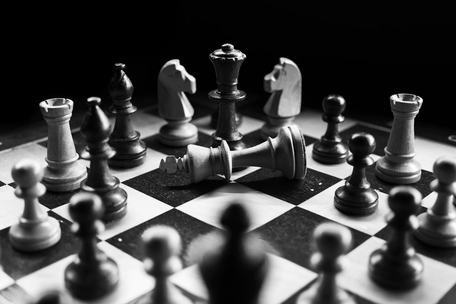 Black and white photo with a chessboard and chess pieces.