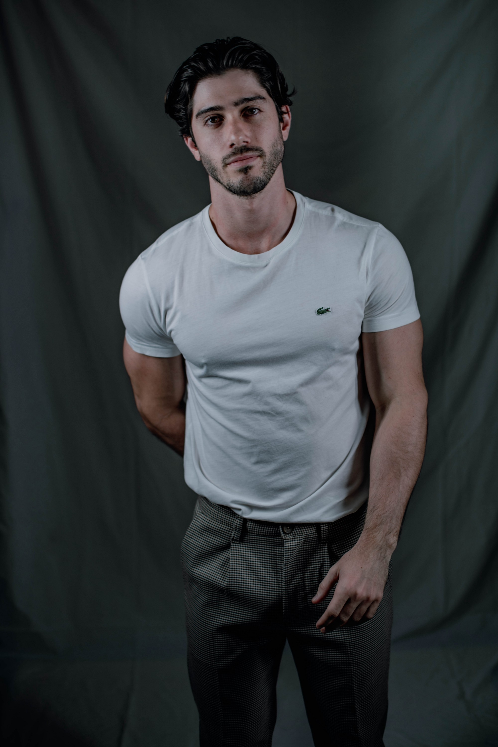 A lightly bearded man in a white T-shirt stands leaning slightly forward. His pecs, biceps, and shoulder muscles show nicely.