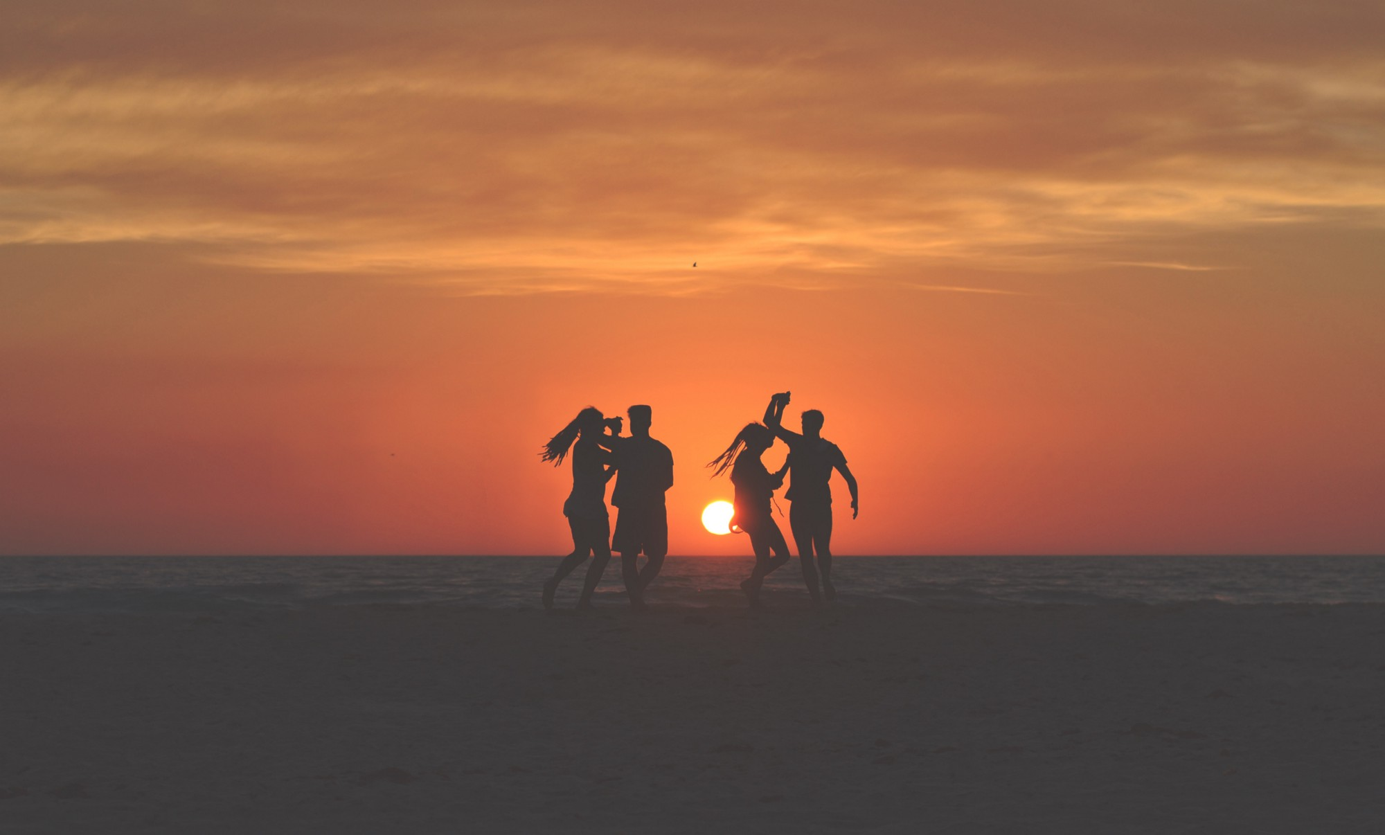 Two couples dancing on a beach