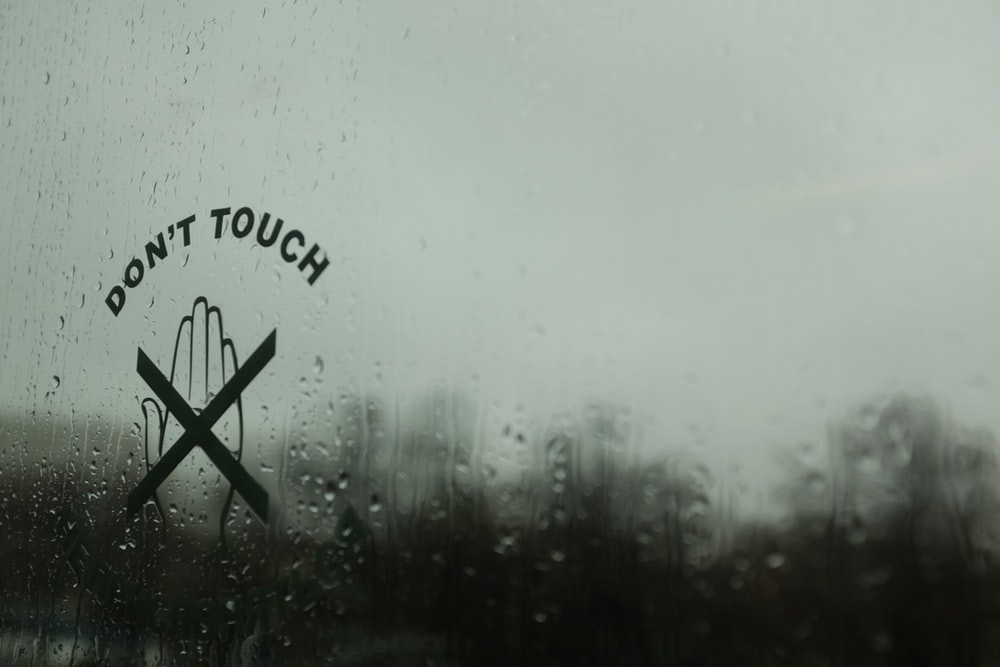 """Picture of a rainy window with a crossed-out hand and text """"Don't touch"""""""