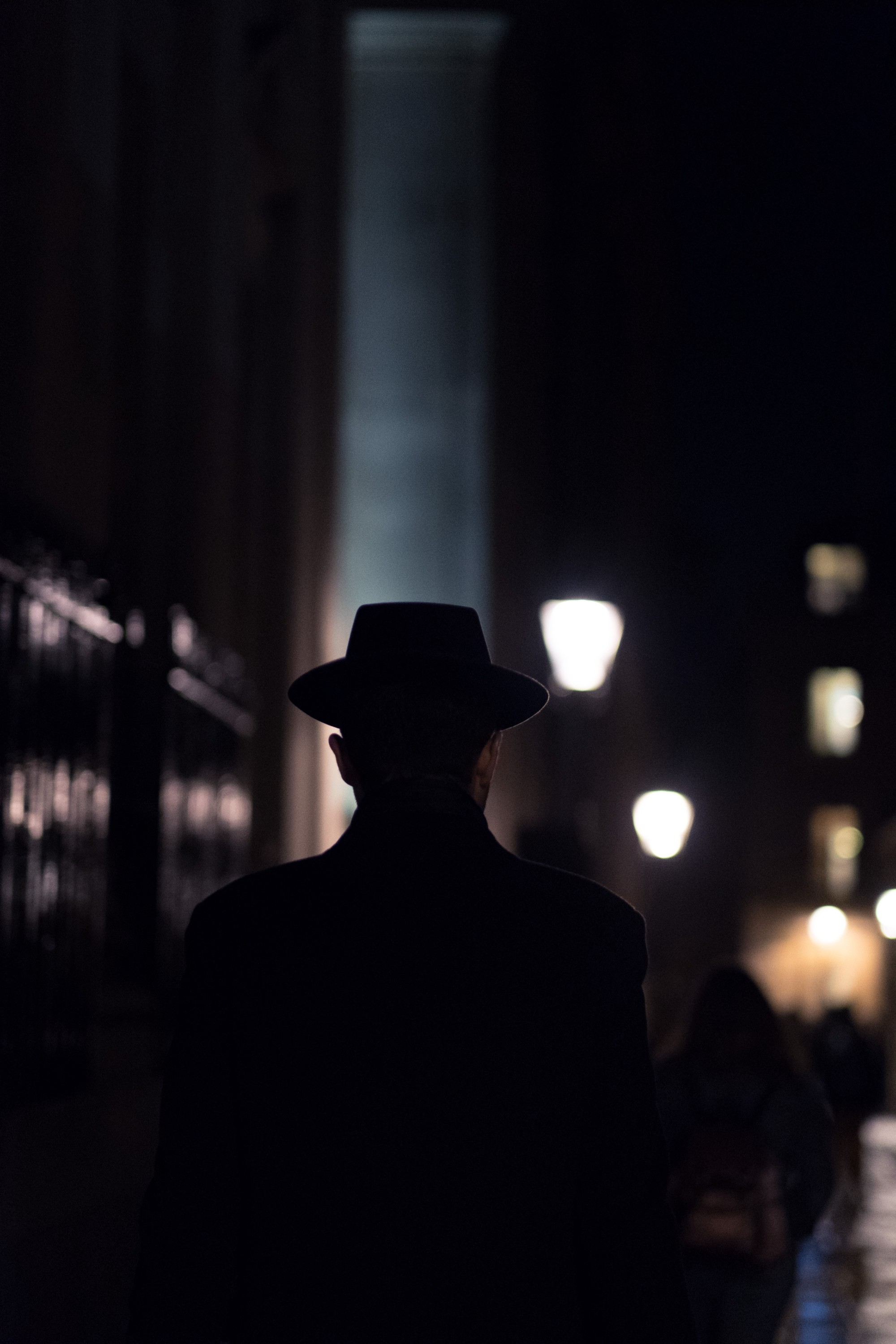 A man wearing a fedora walking at night light slightly by street lamps