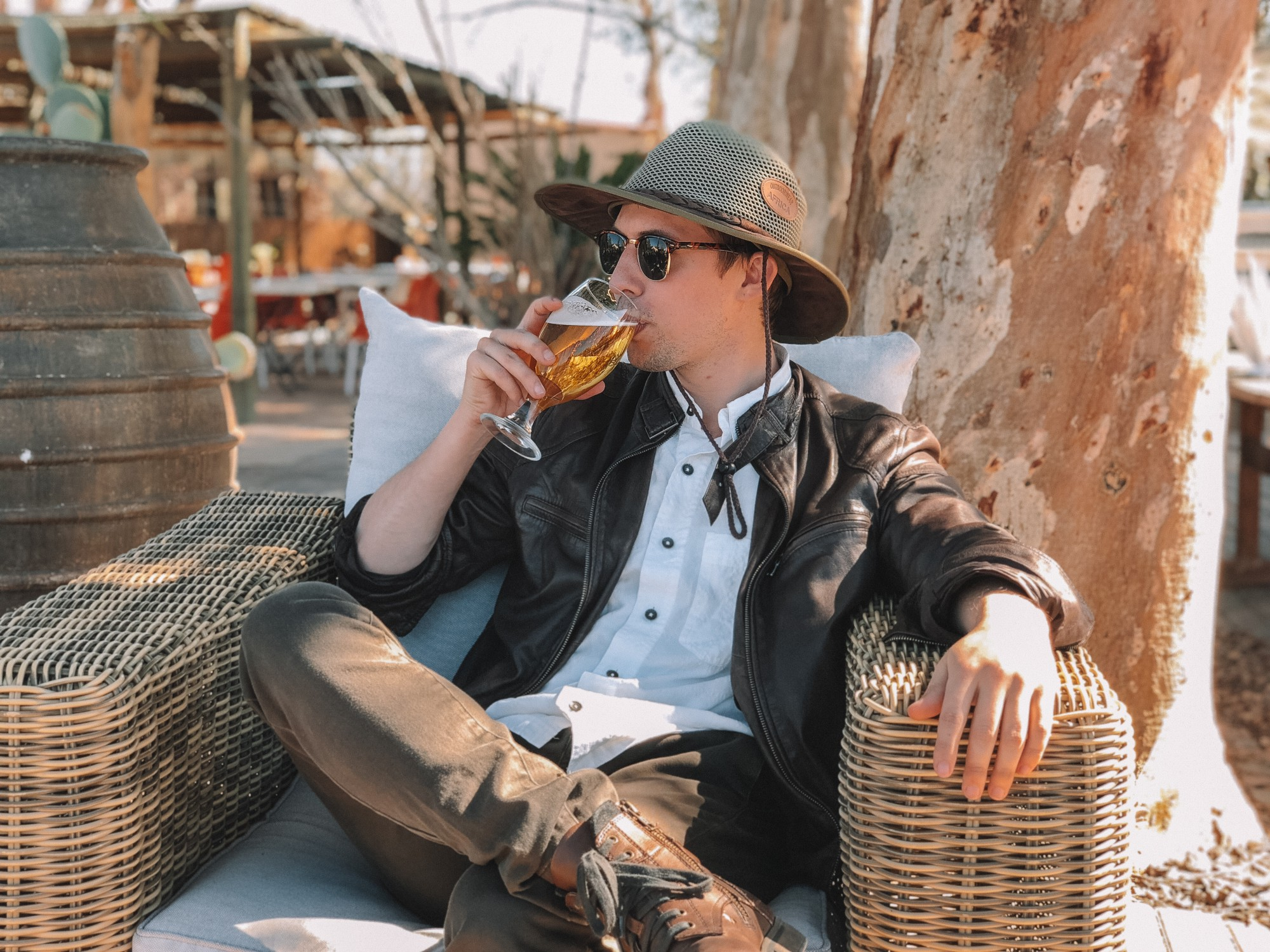 Man with a hat and shades sipping alcohol seated on a cane chair