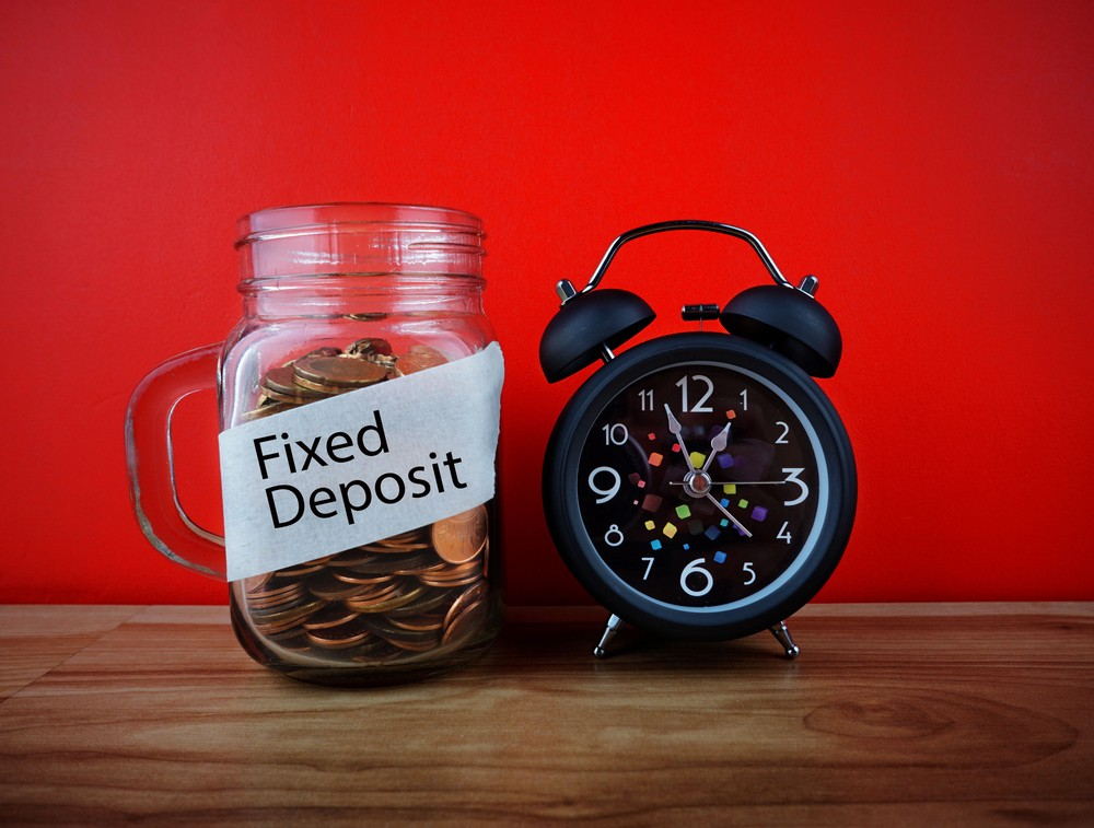 Jar with a label that says 'Fixed Deposit' with a clock to indicate the term. Fixed deposit is one type of fixed income investment option.